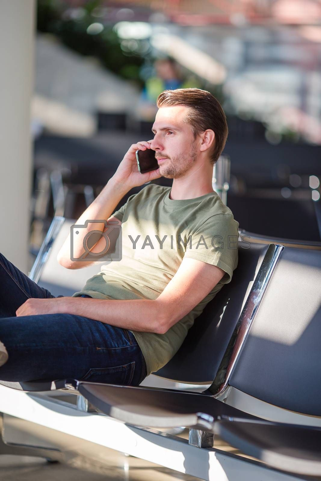 Passenger in an airport lounge waiting for flight aircraft. Young man talking by smartphone in airport waiting for boarding