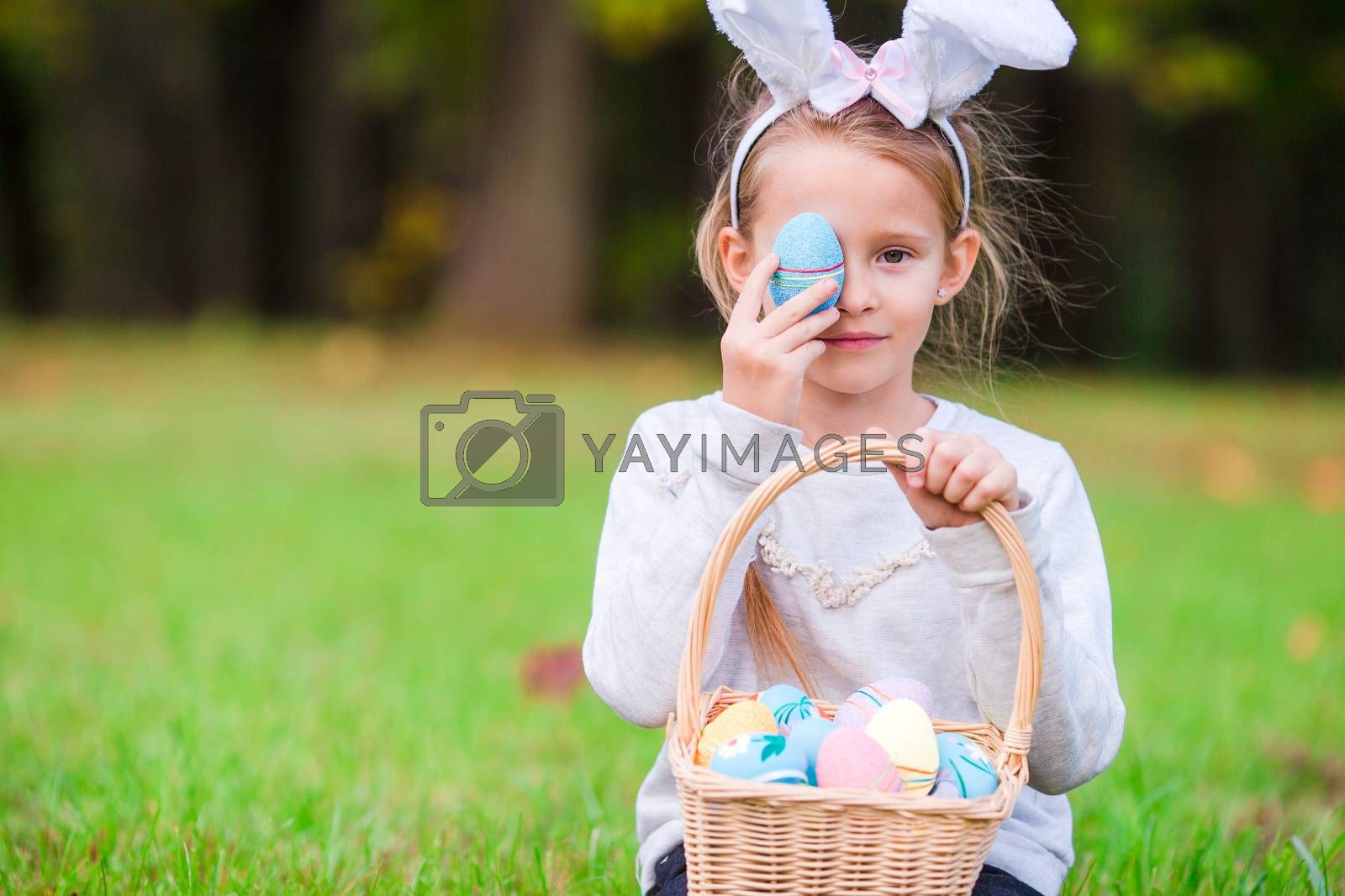 Adorable girl wearing bunny ears holding basket with Easter eggs