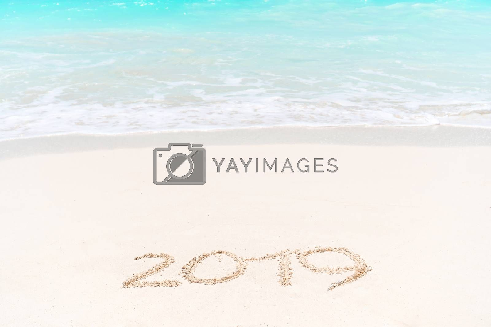 2019 handwritten on sandy beach with soft ocean wave on background by travnikovstudio