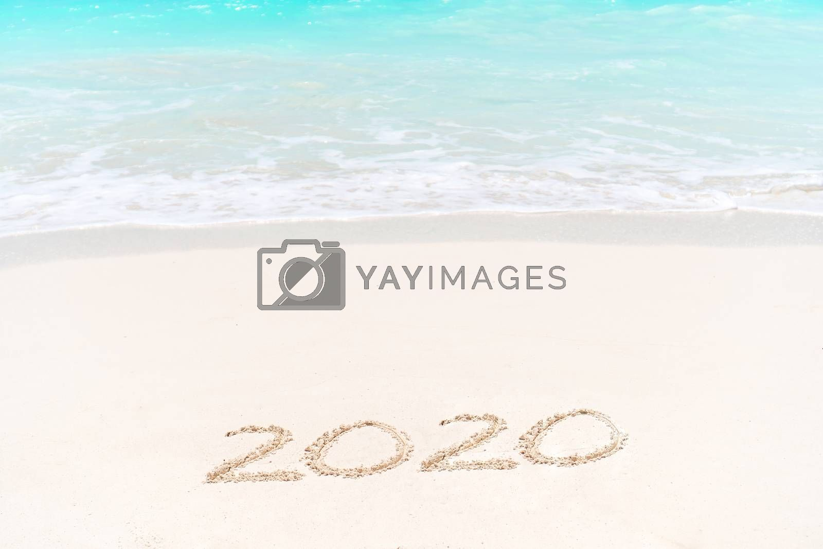 2020 handwritten on sandy beach with soft ocean wave on background by travnikovstudio