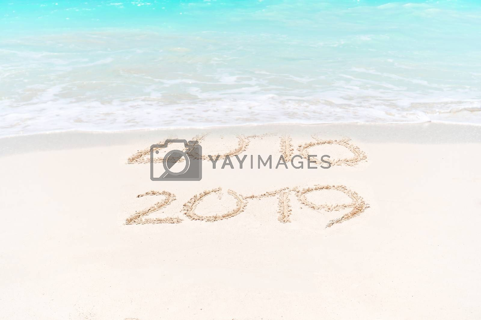 number handwritten on sandy beach with soft ocean wave on background