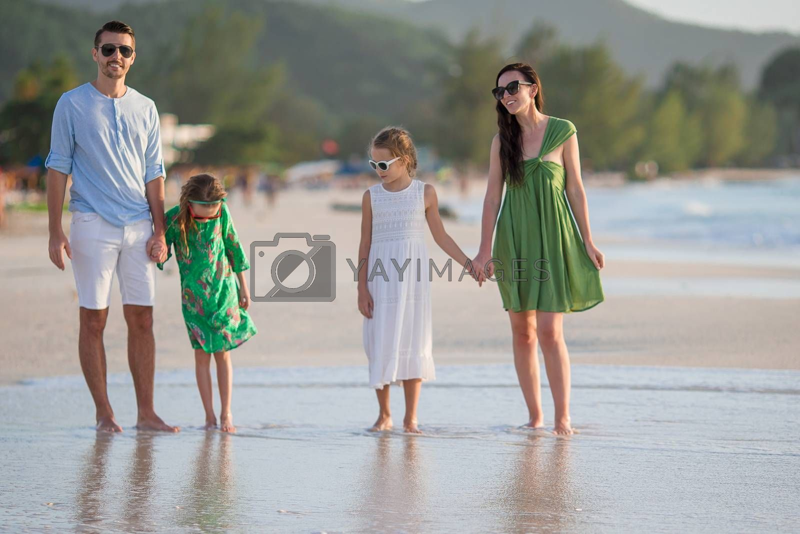 Family of four in the sunset on beach vacation