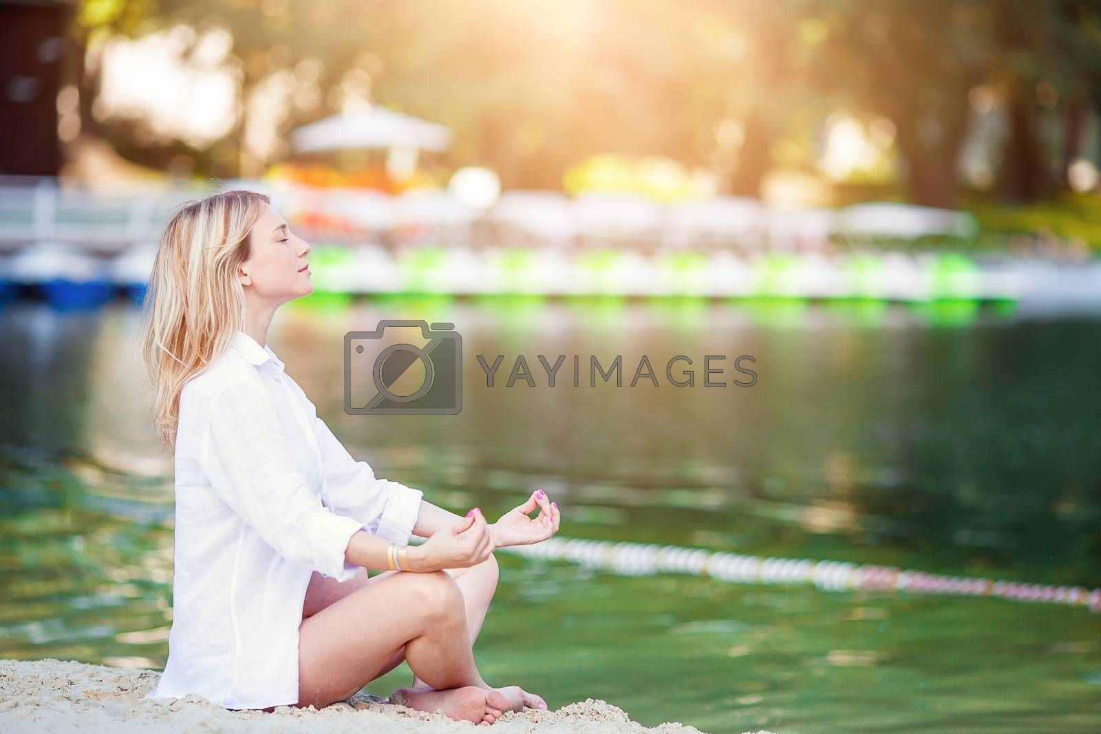 Pregnant beautiful young woman in lotus position on the lake relaxes. Pregnancy concept - pregnant girl in white shirt over sunny summer background