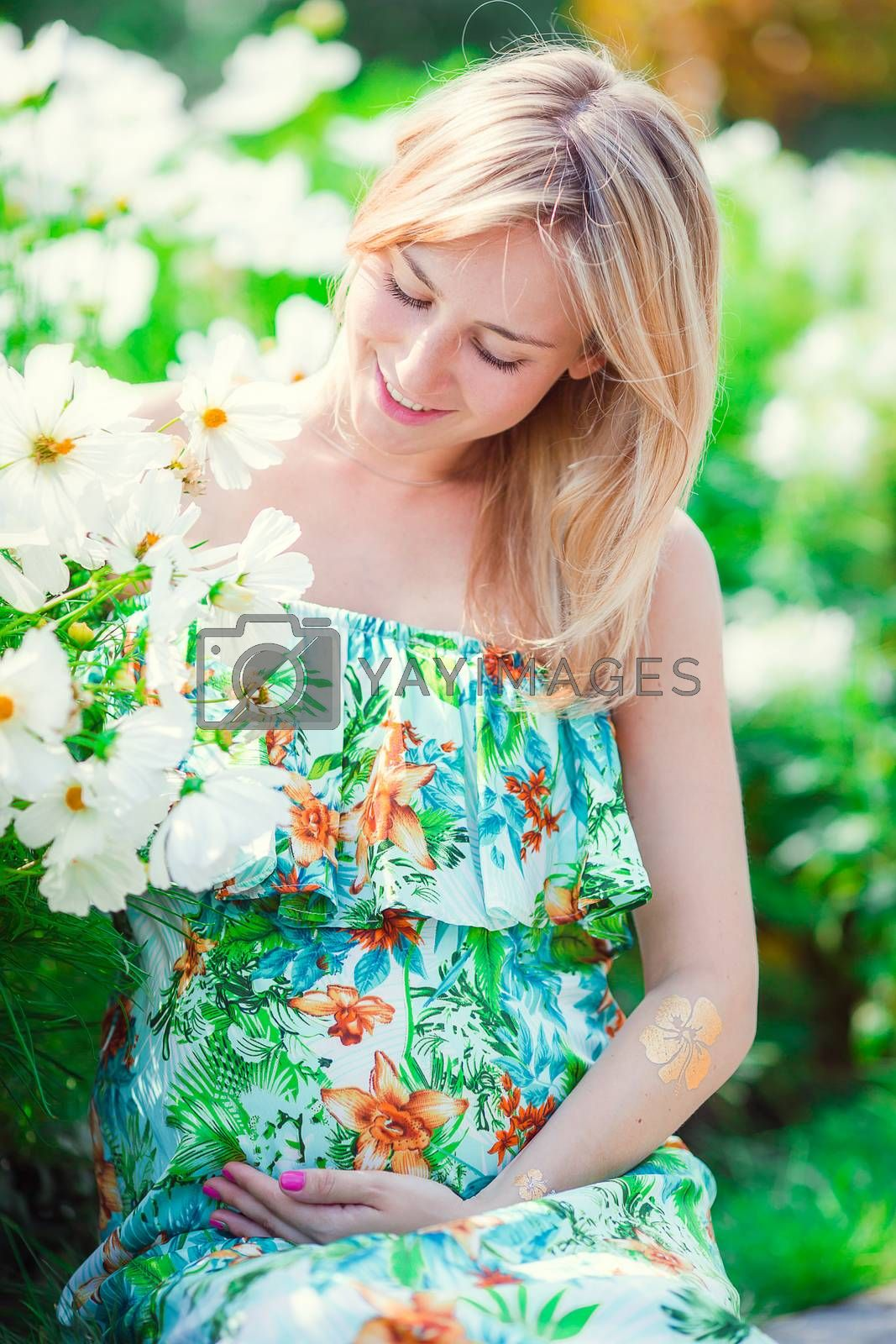 Lovely tender pregnant woman relaxing resting on the grass in the park on a warm day. Pregnancy concept
