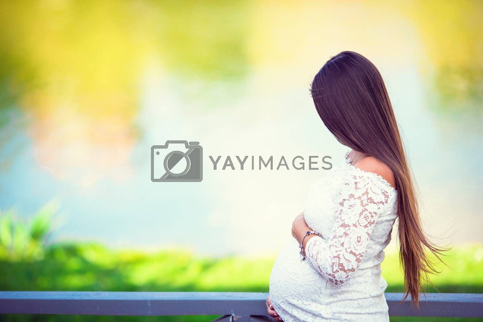 Beautiful pregnant woman with long hair outdoors