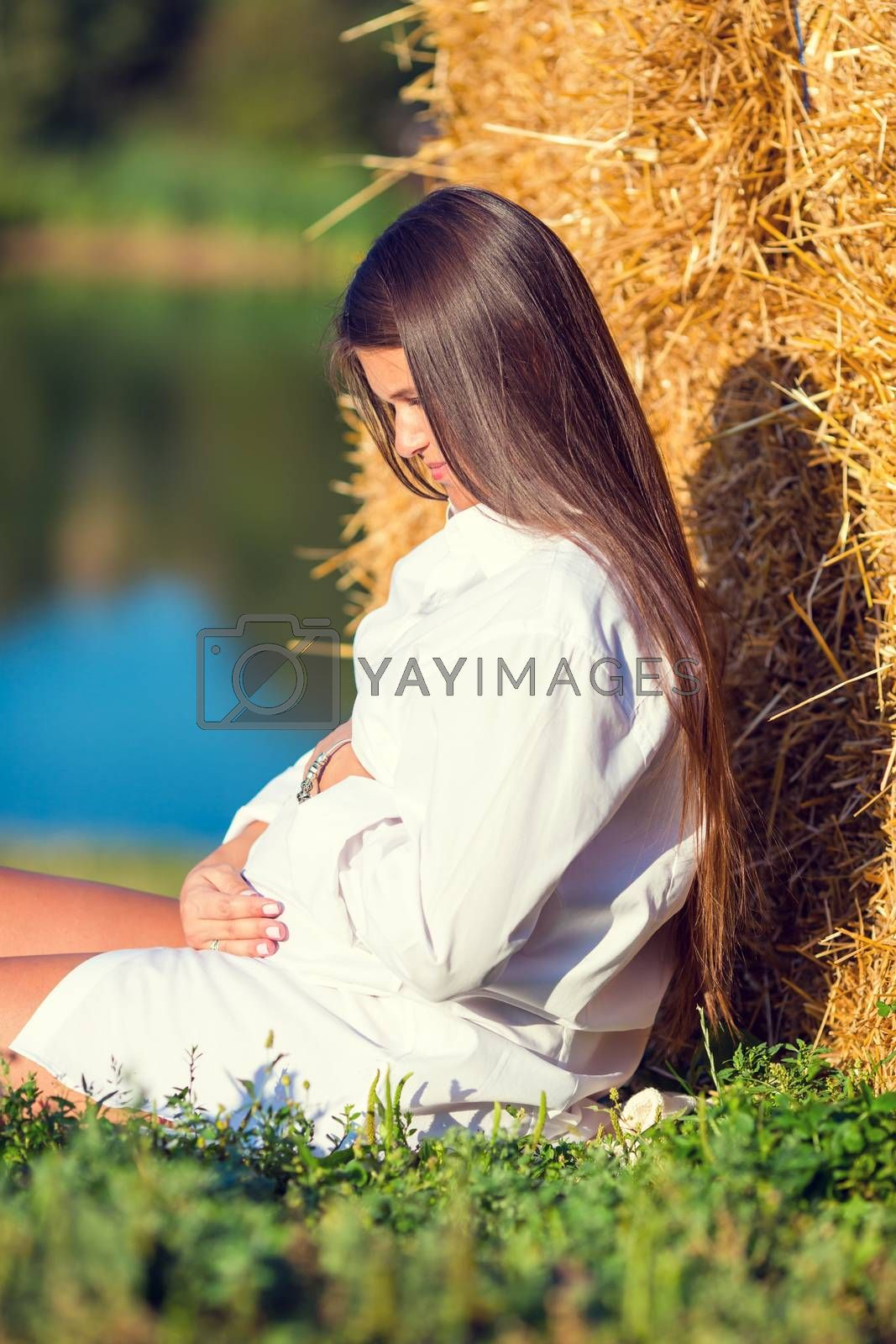Beautiful pregnant woman outdoor near the lake. Pregnancy concept - pregnant woman in white shirt holding on belly relaxing on the grass