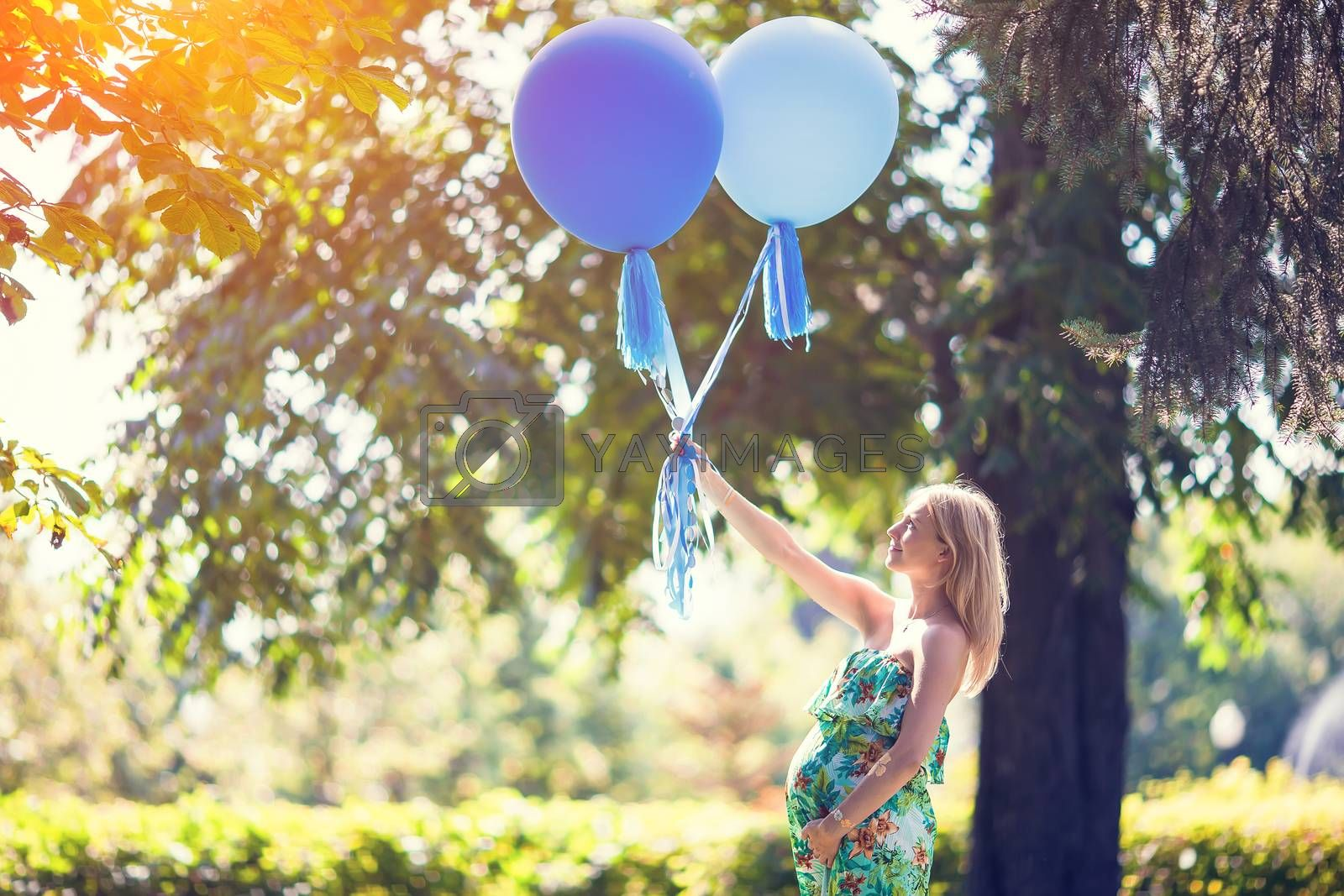 Pregnant woman with a bunch of balloons in outdoor park