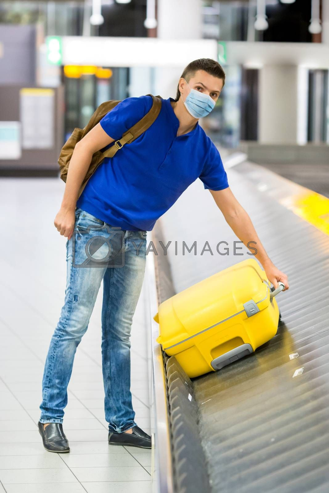 Man wearing a mask for prevent virus picks up his luggage from the tape at the international airport. Protection against Coronavirus and gripp