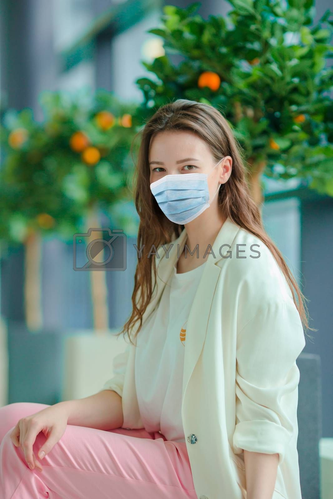 Tourist girl wearing a mask for prevent virus with baggage in international airport. Protection against Coronavirus and gripp