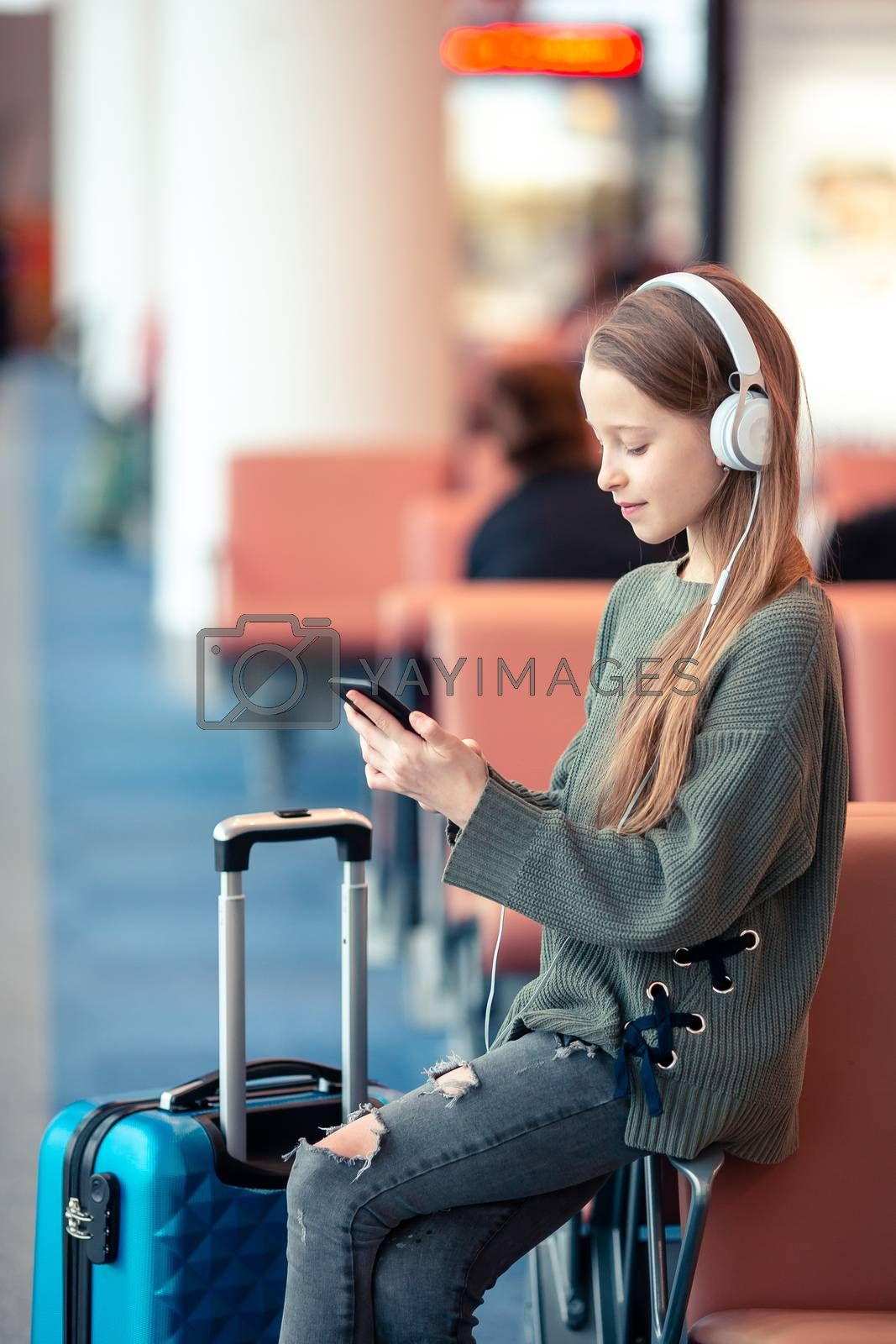 Little adorable kid in airport waiting for boarding indoors with phone in hands