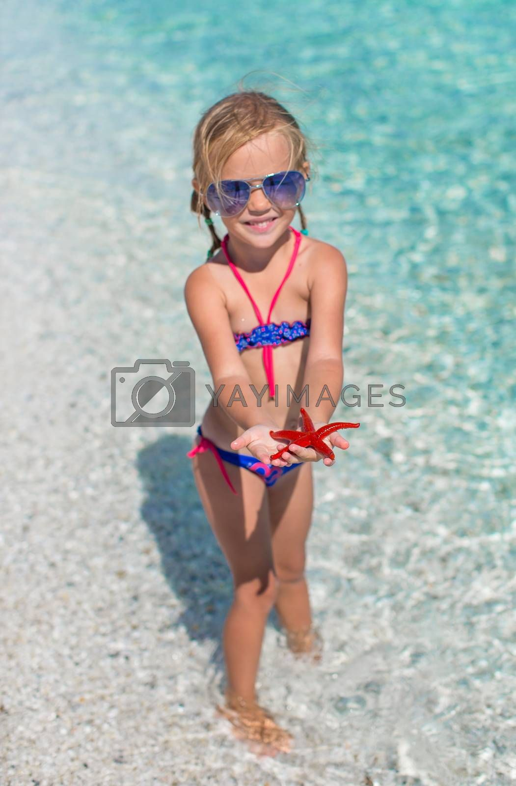 Little adorable girl with sea star at the tropical beach by travnikovstudio