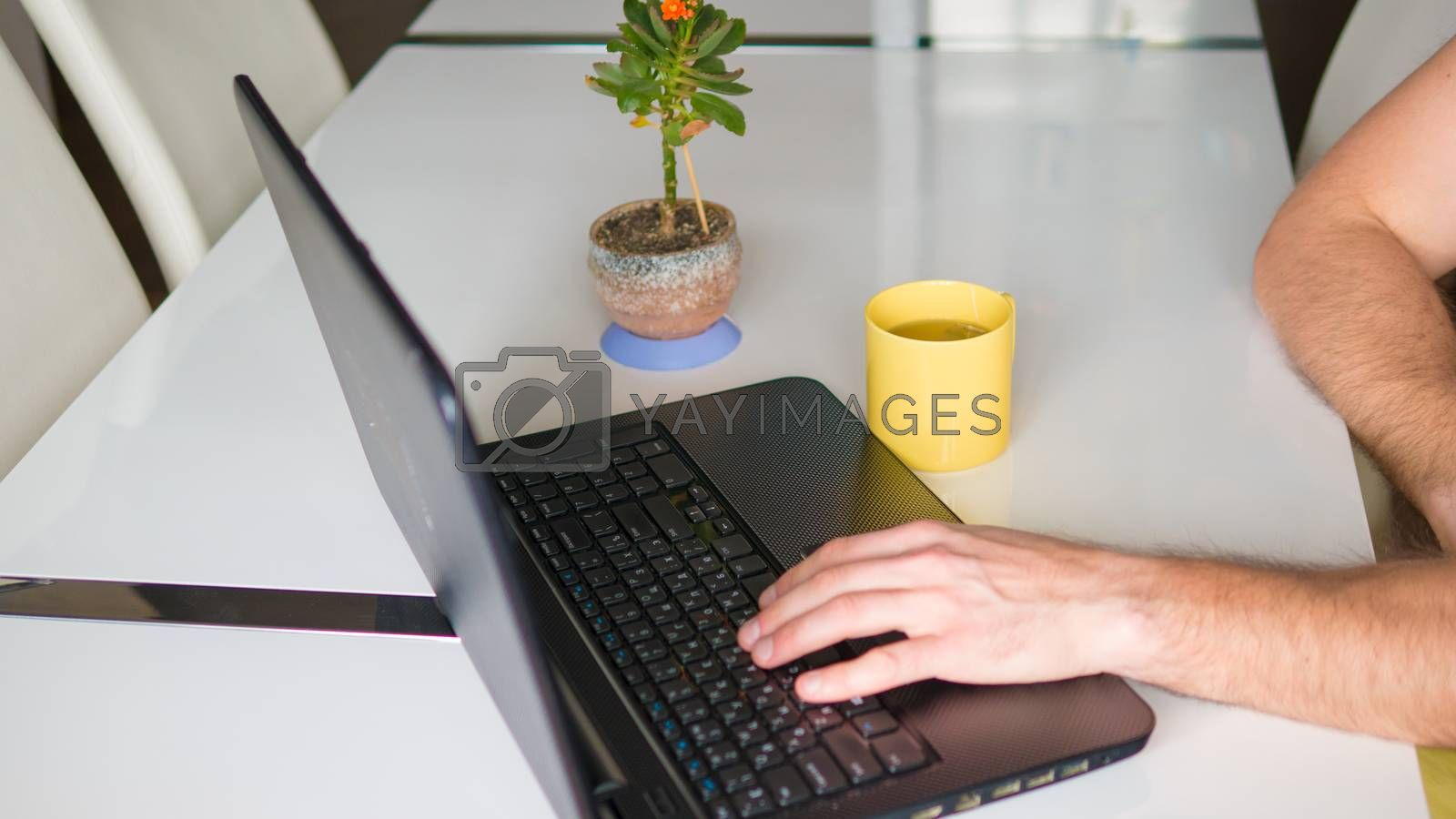 typing in a laptop at a desk a yellow cup on the table male hands print