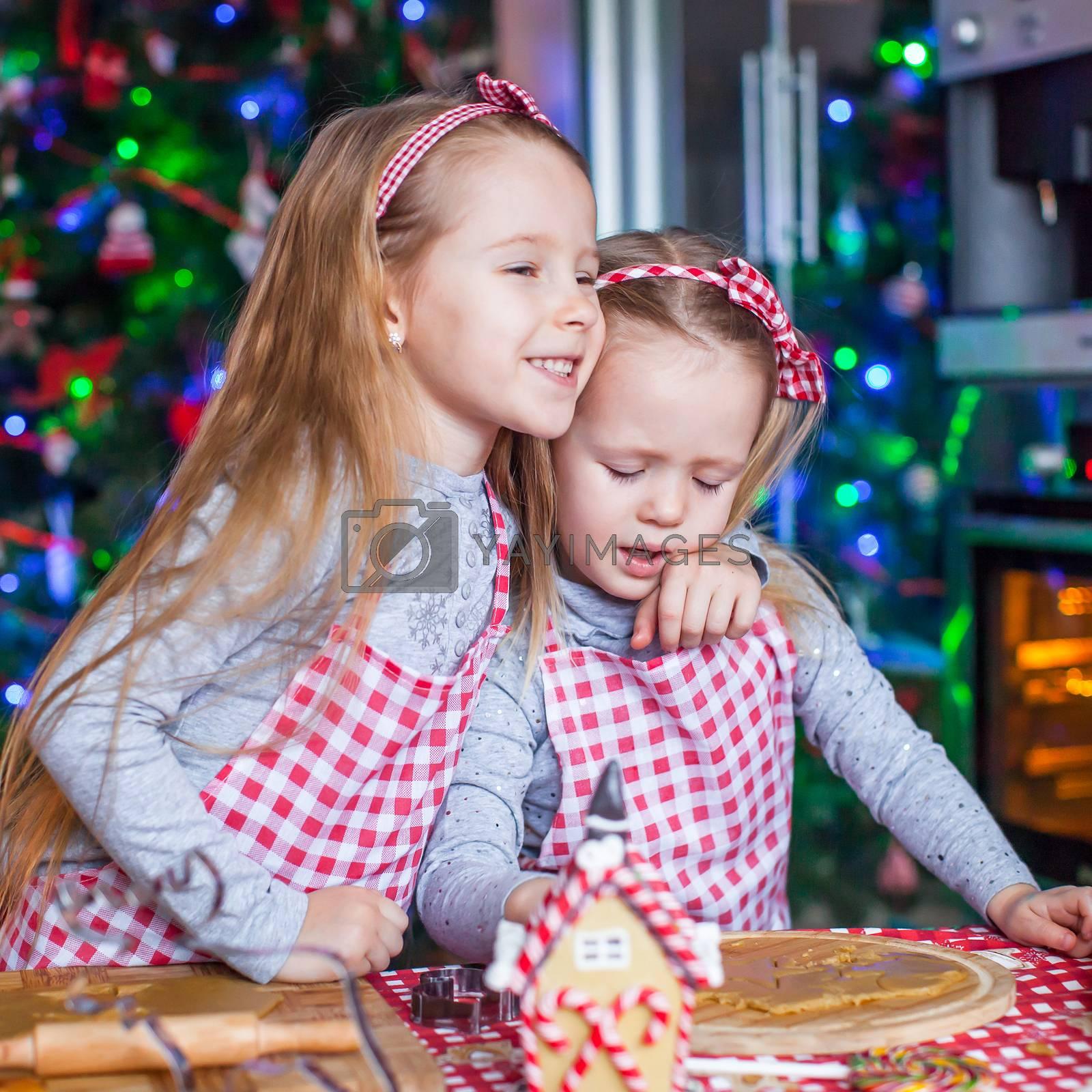 Cute girls preparing gingerbread cookies for Christmas