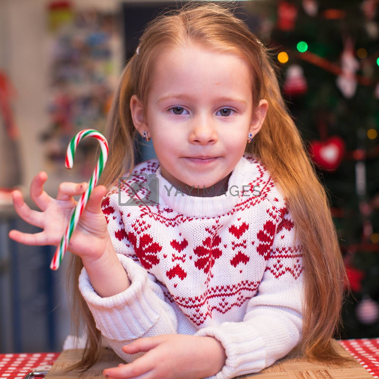 Little girl with candy in hand will prepare Christmas cakes