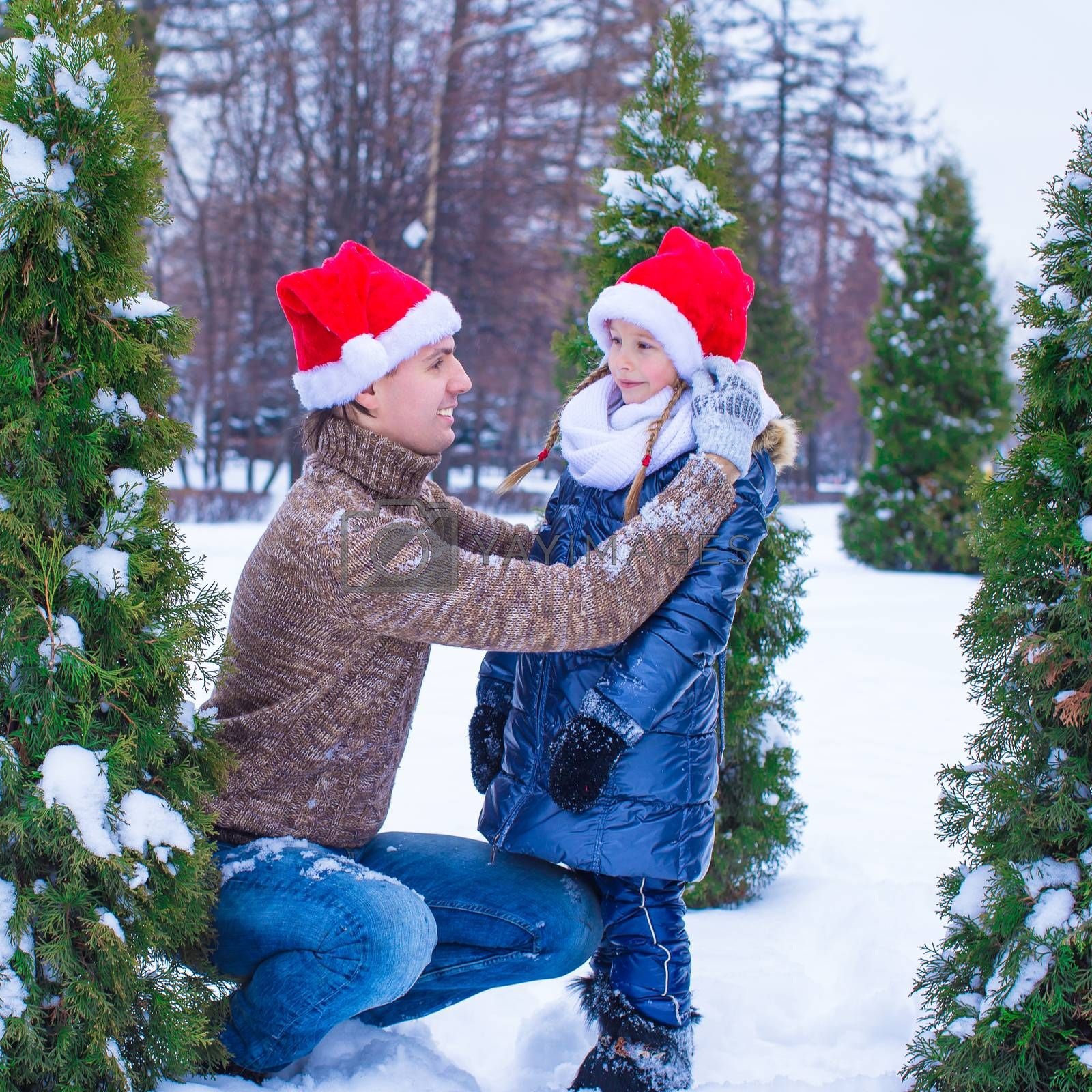 Happy father and kid in Santa hats with christmas tree decorations outdoor