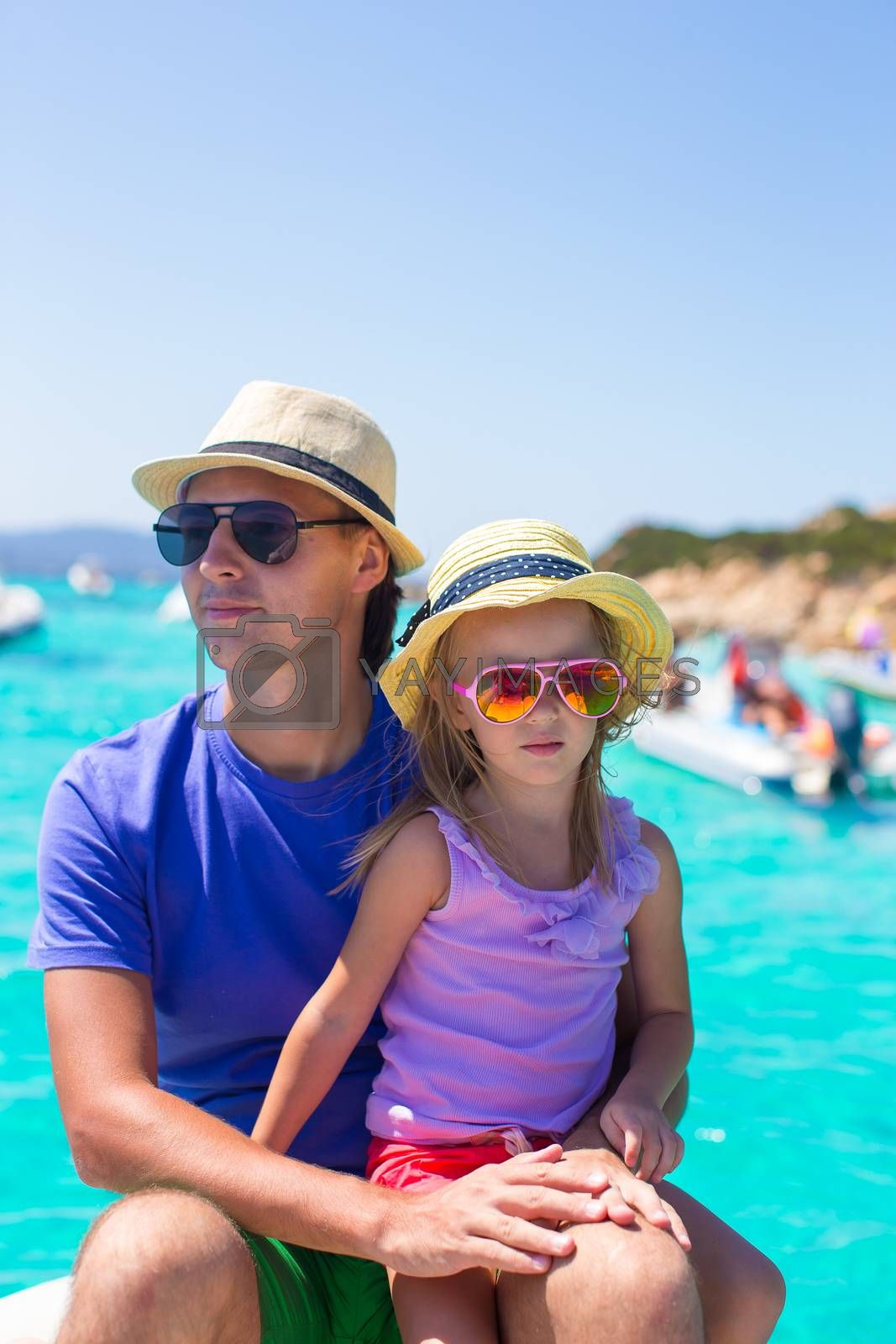 Young father with adorable girl resting on big boat
