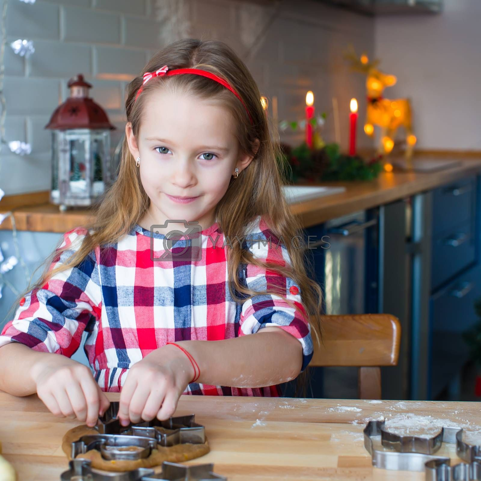 Little adorable girl baking Christmas cookies at home indoor