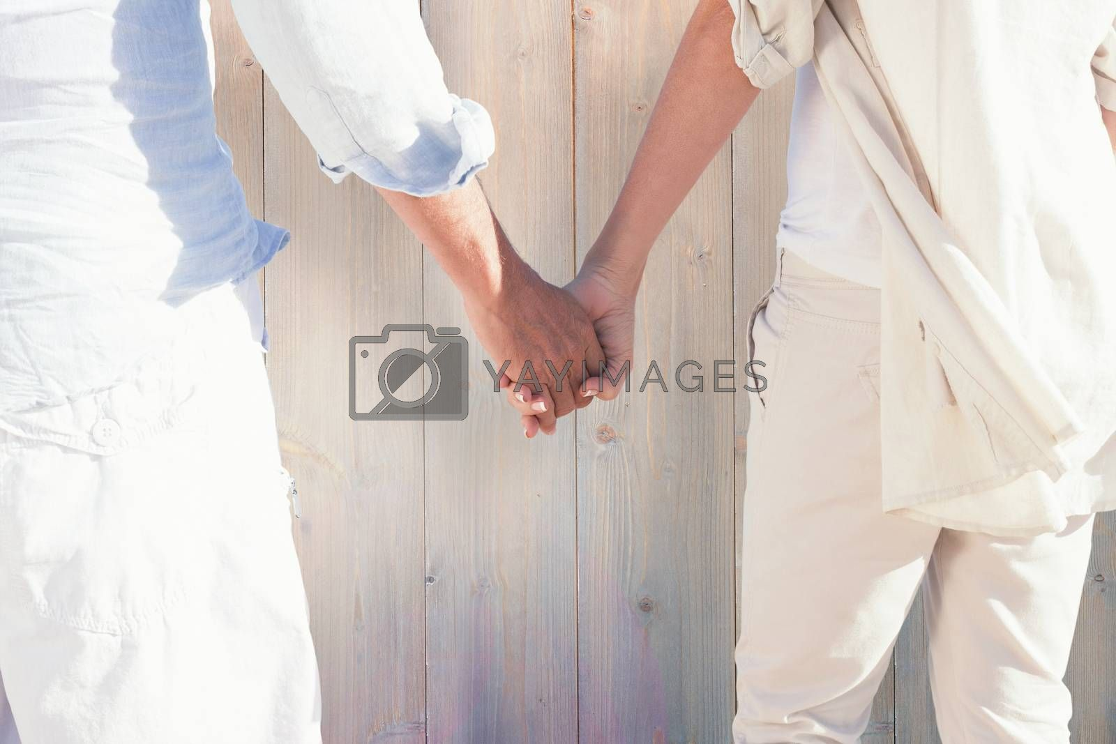 Couple on the beach looking out to sea holding hands against pale grey wooden planks