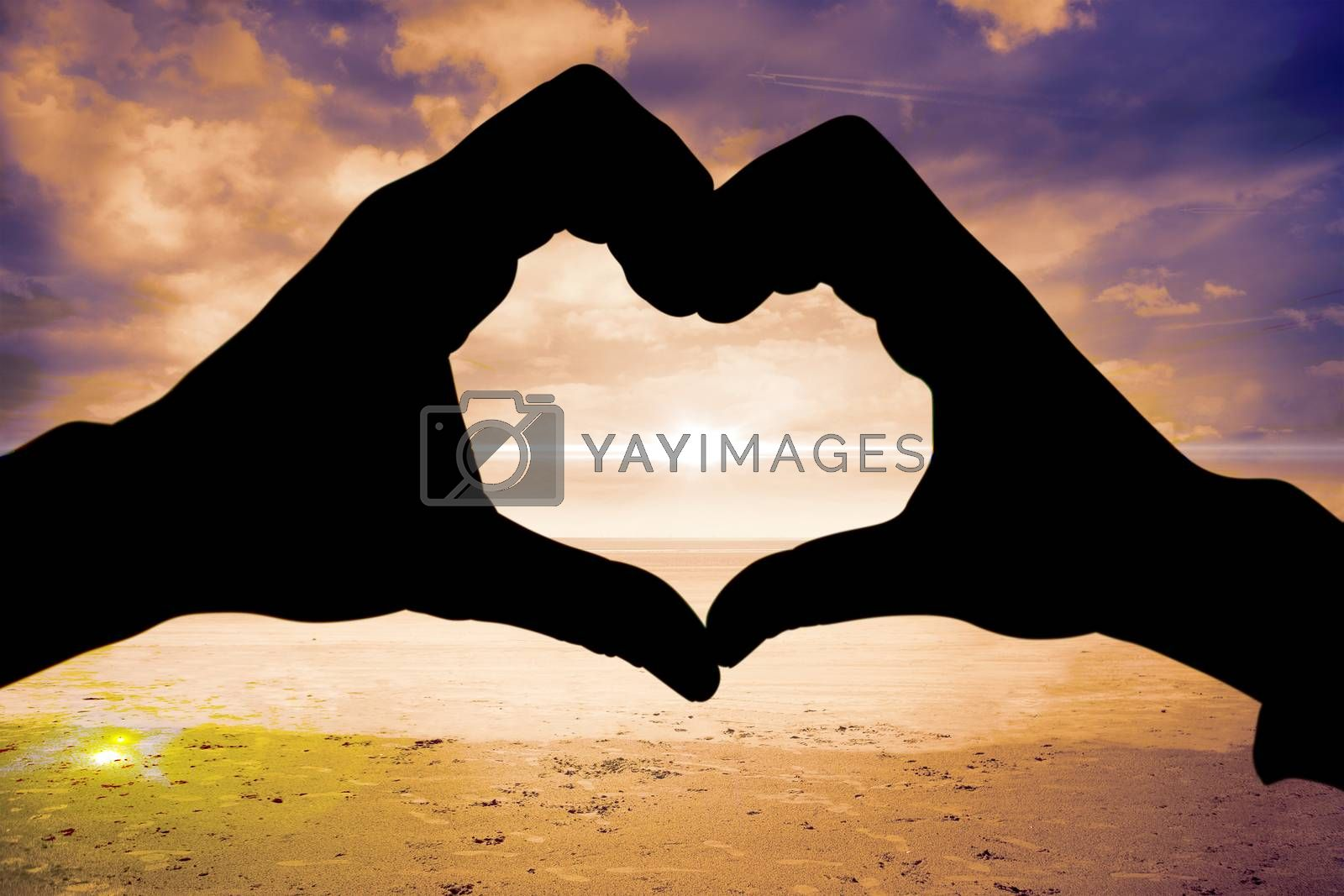 Couple making heart shape with hands against serene beach landscape