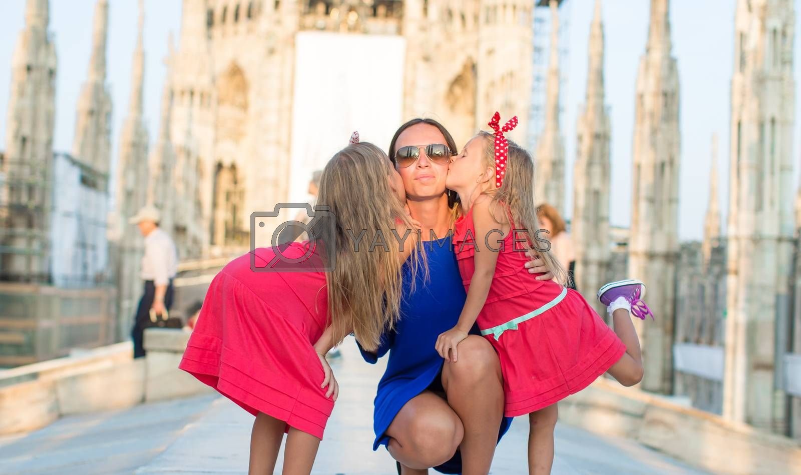 Adorable little girl with mother on rooftop of Duomo, Milan, Italy