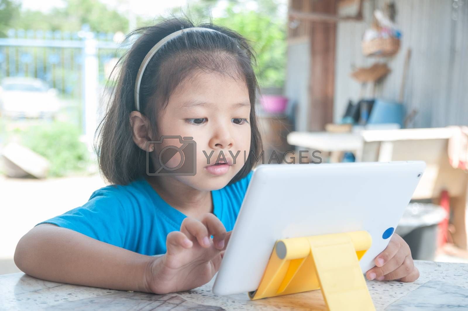 Asian Girl learning online course or playing game online on Digital Wireless Device or Tablet at home as Technology e-learning concept.