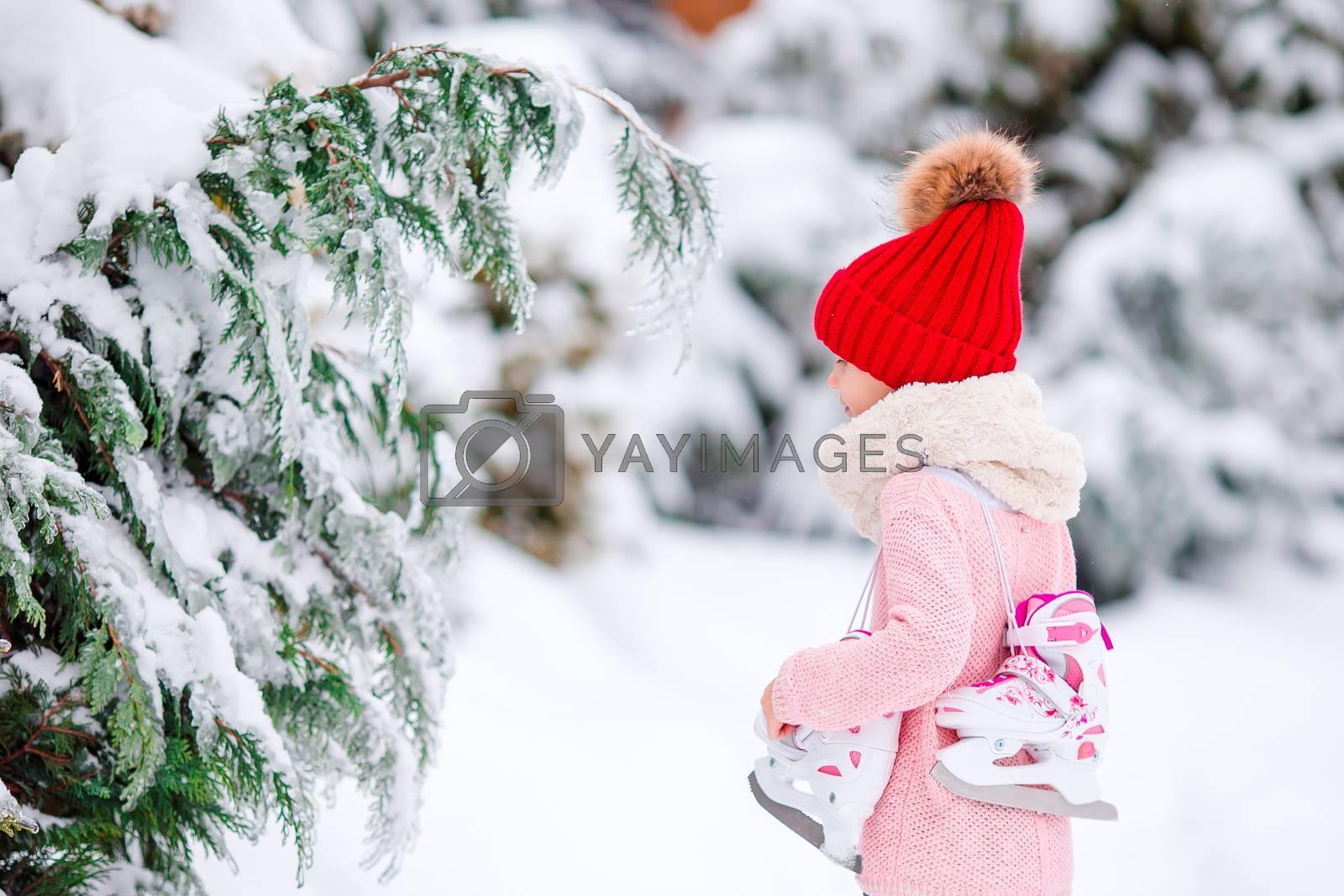 Cute little kid girl is going skate outdoors. by travnikovstudio