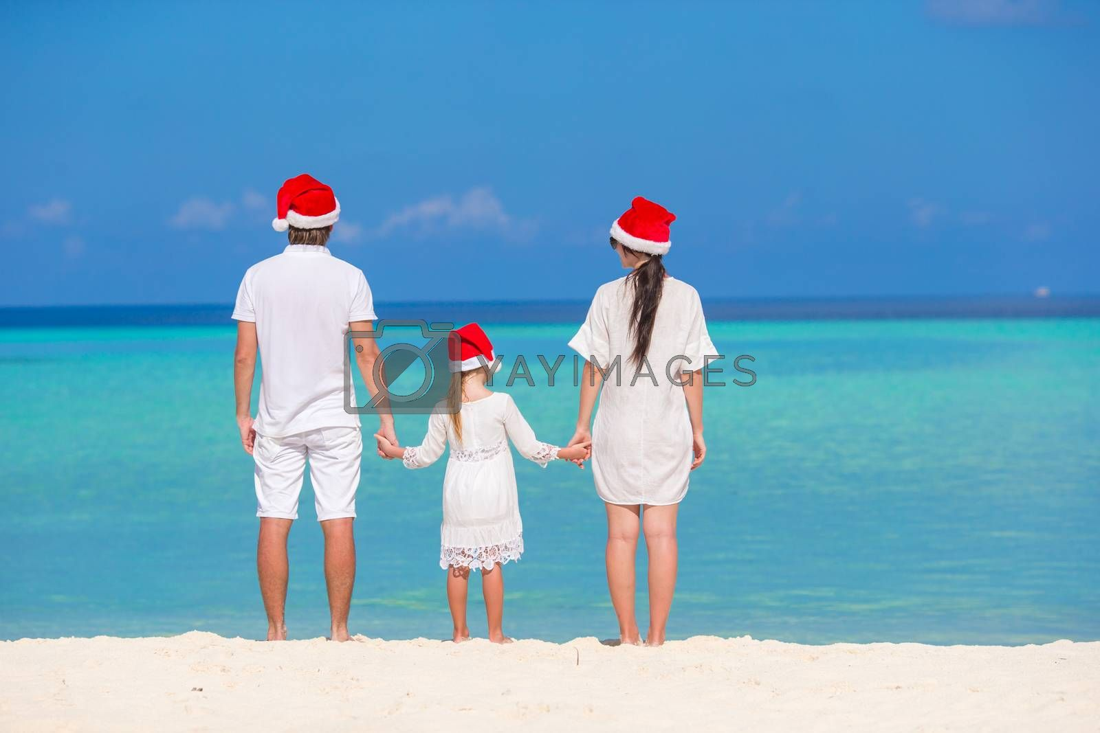 Happy family of three in Christmas Hats during tropical vacation