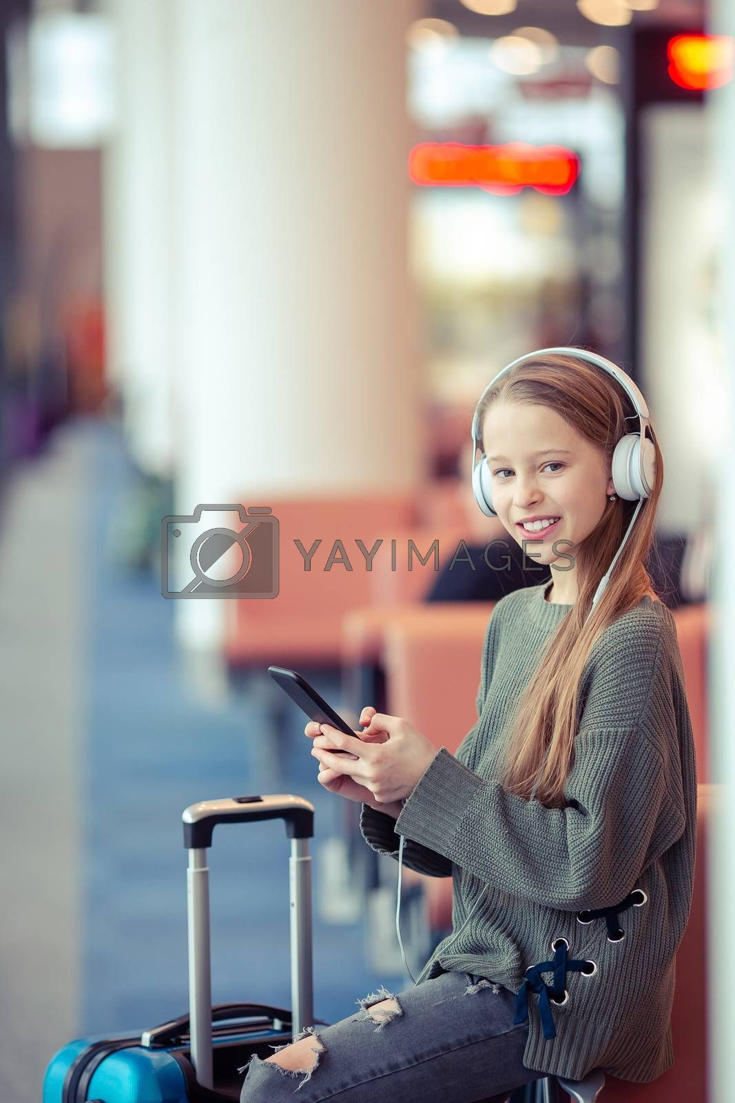 Little adorable kid in airport waiting for boarding indoors. Adorable little girl at airport listening the music