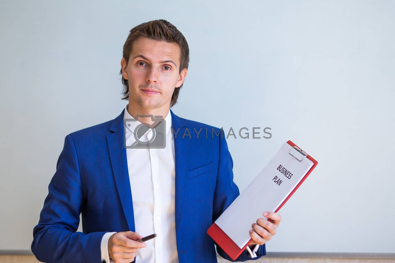 Young businessman with business plan and financial documents in his office by travnikovstudio