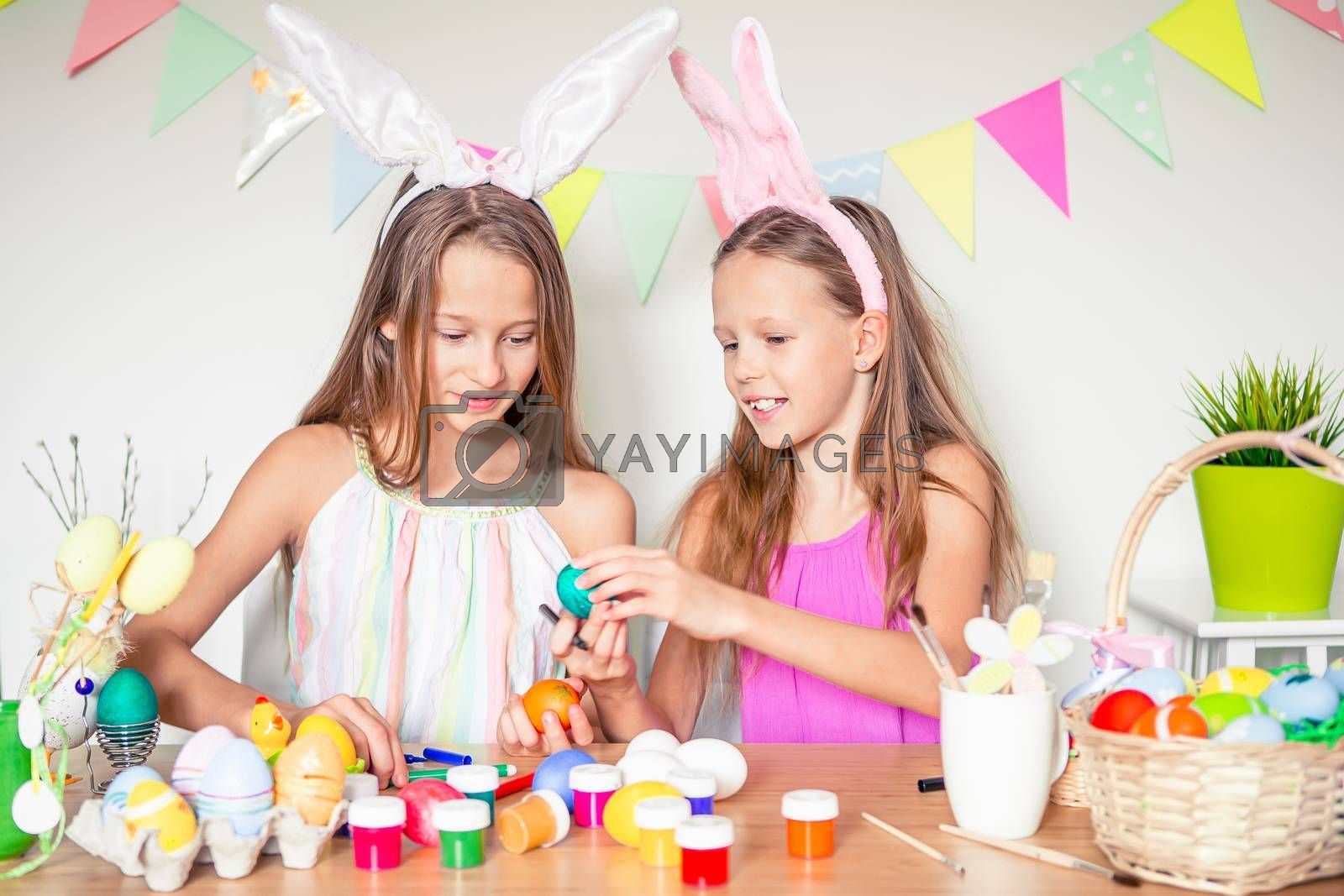 Happy Easter. Children painting Easter eggs and having fun on Easter day.