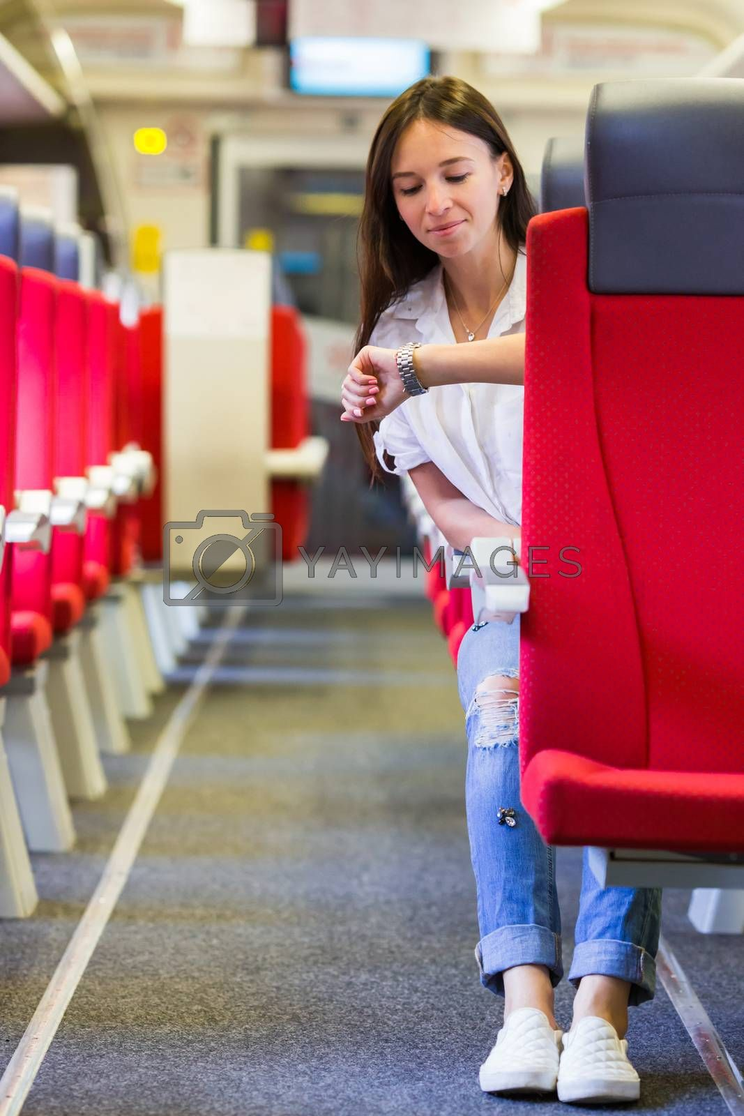 Young woman talking on the phone and listen music traveling by train