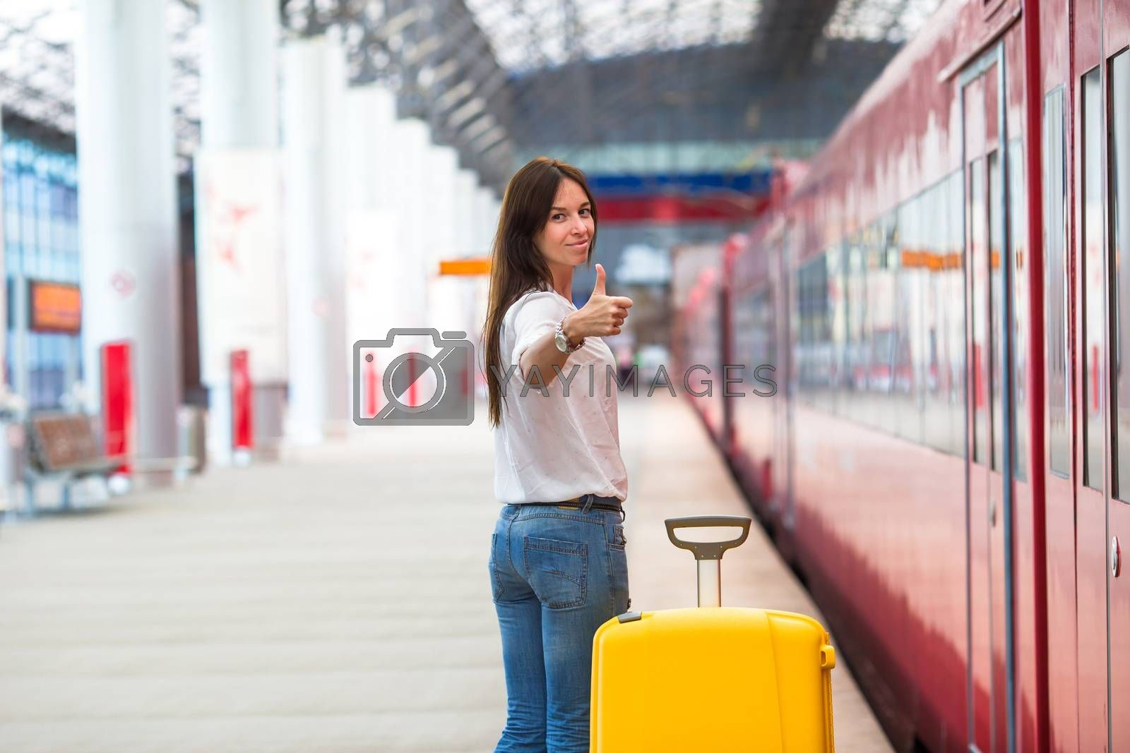 Young woman with luggage on the platform waiting for aeroexpress
