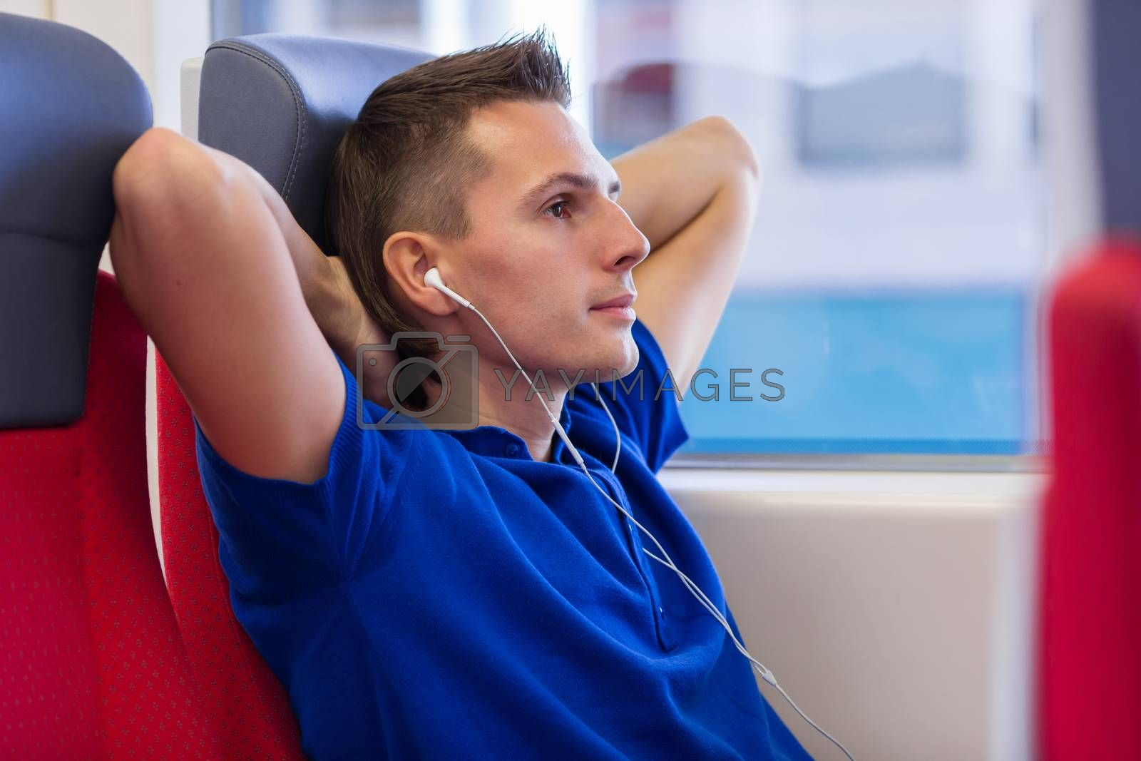 Young man talking on the phone and listen music traveling by train