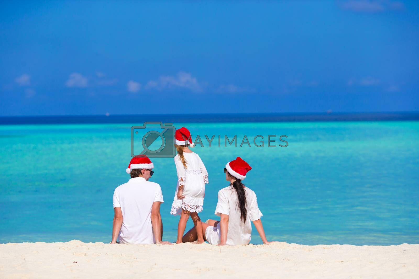 Happy family of three in Santa Hats during tropical vacation