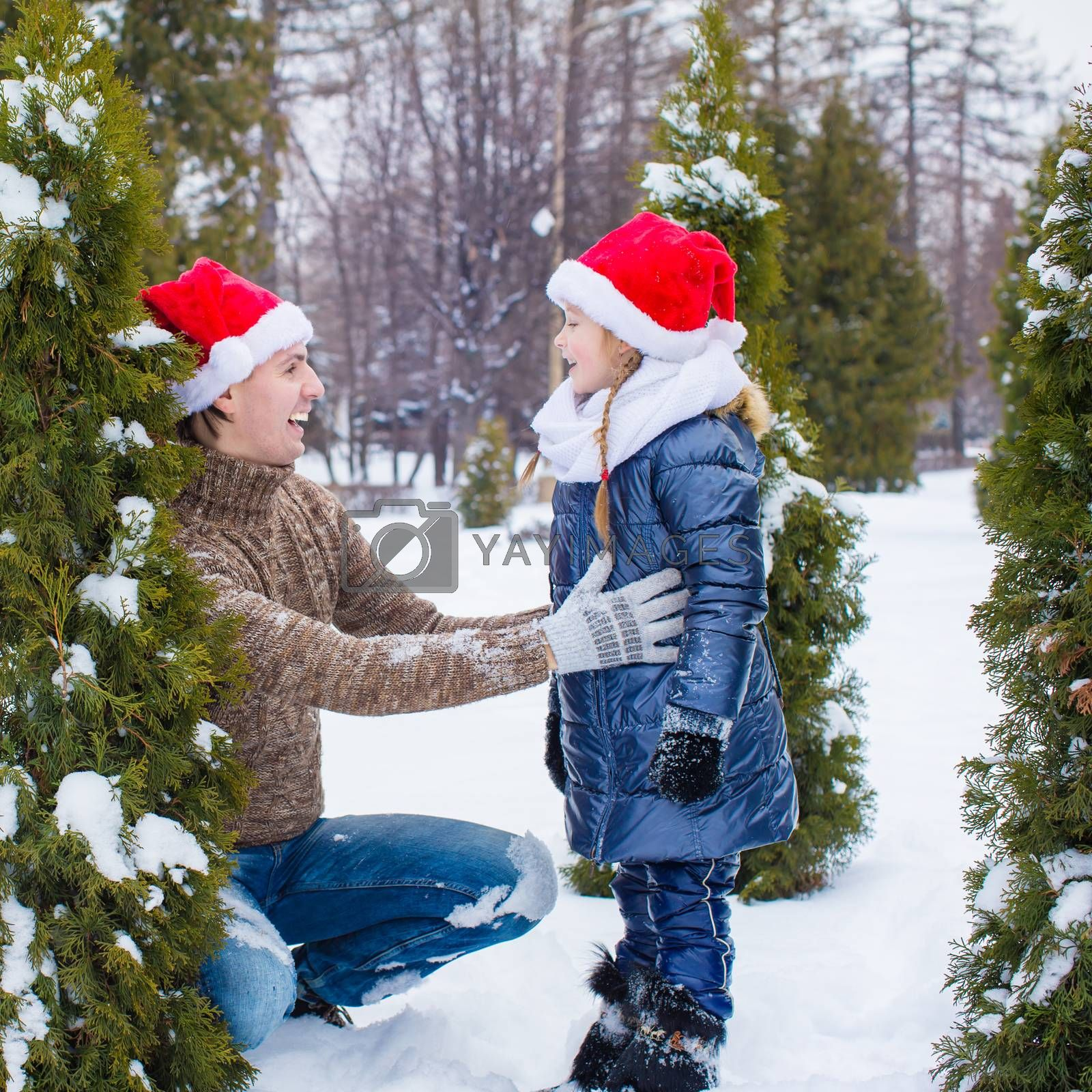 Happy family of two in Santa hats with christmas tree outdoor
