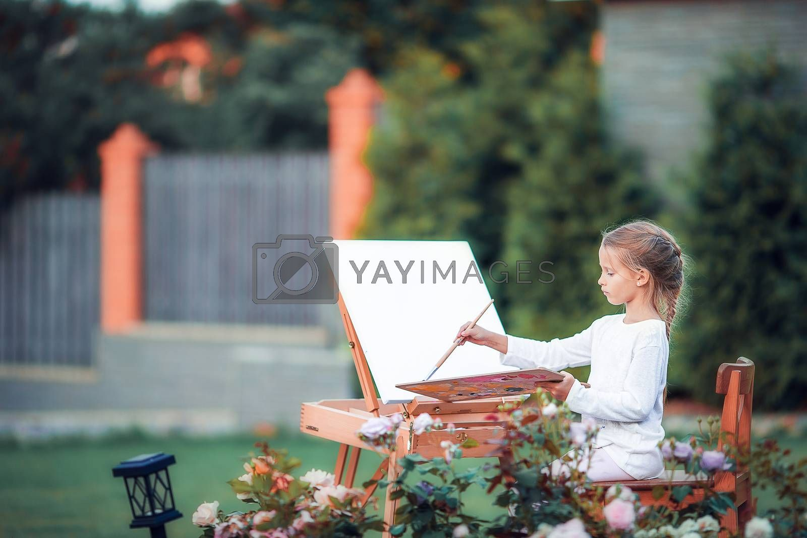 Happy girl painting a picture on an easel on a warm day