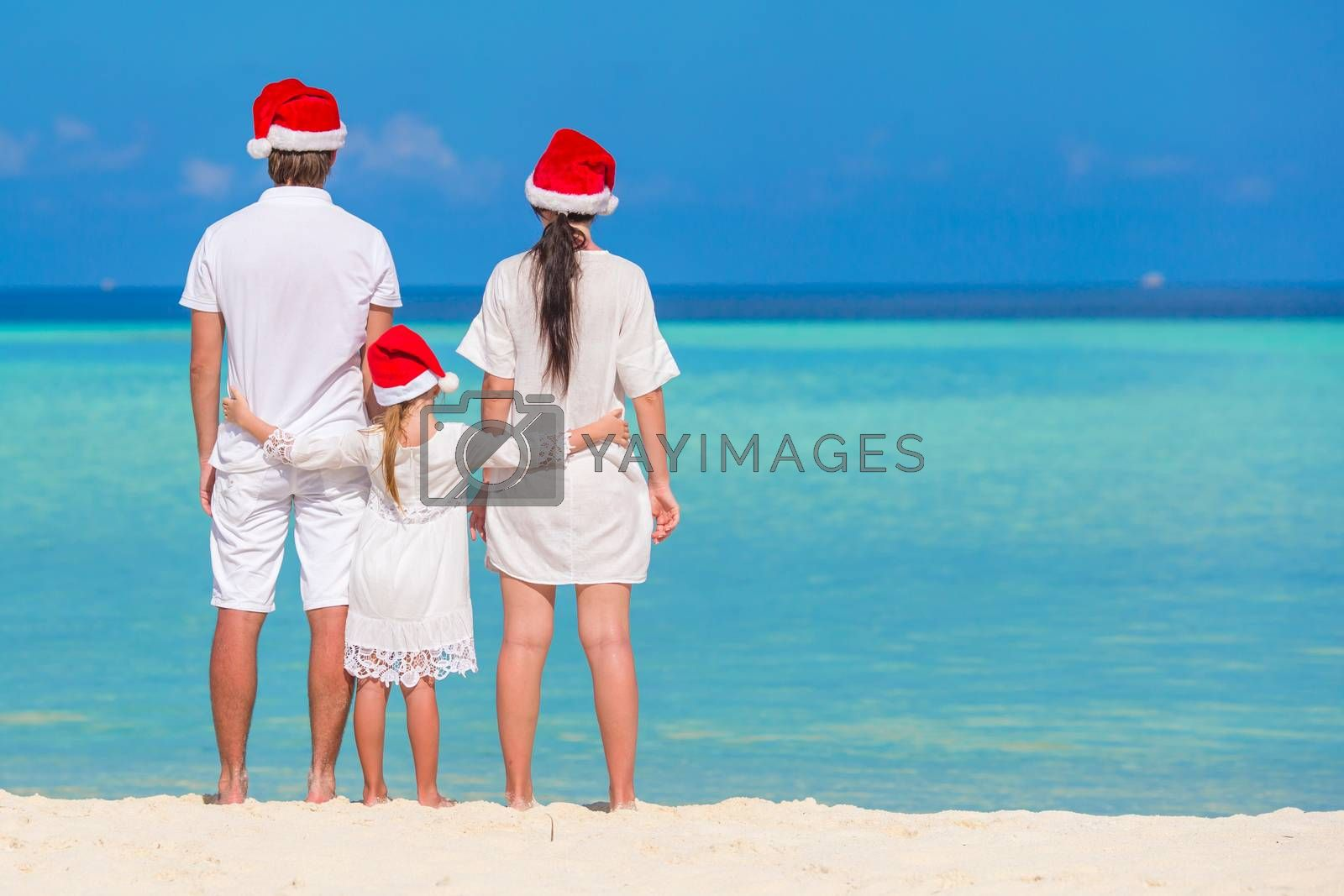 Happy family in Santa Hats on beach during Christmas vacation