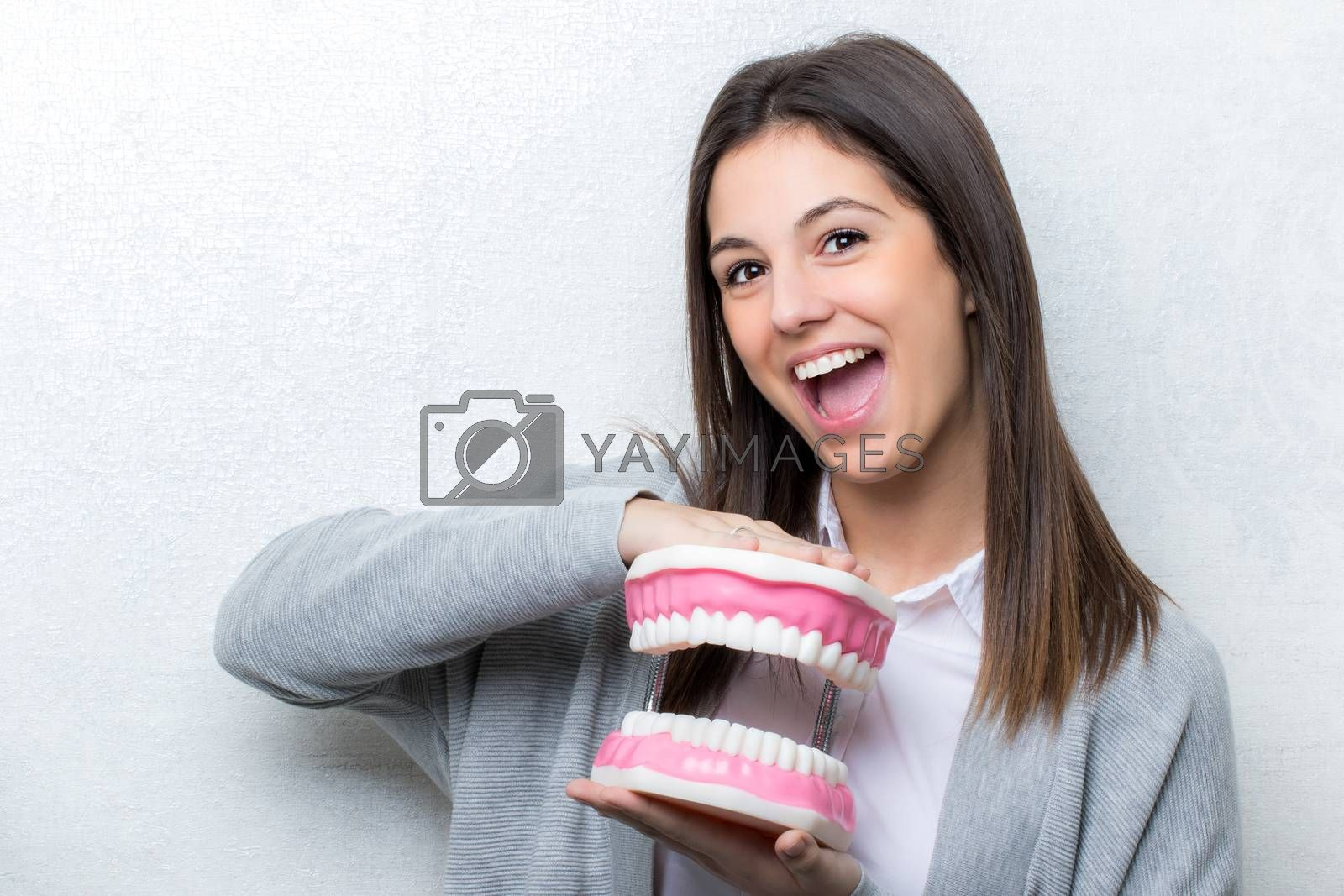 Close up portrait of attractive young girl holding oversize human teeth prosthesis.Woman  with open mouth facial expression against seamless light background.