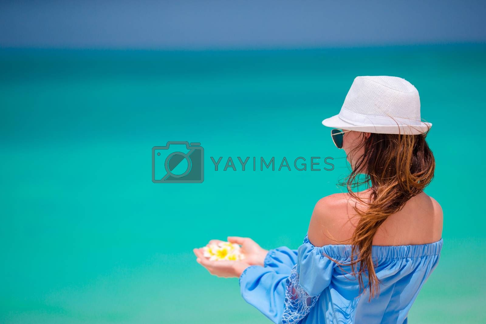 Beautiful frangipani flowers in female hands background turquoise sea on white beach by travnikovstudio
