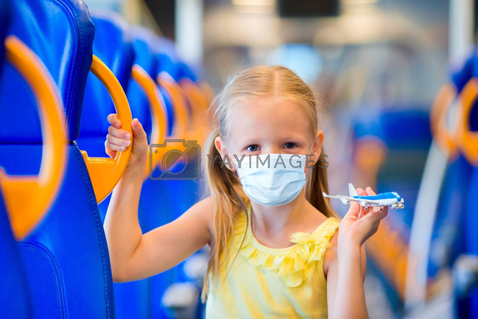Little girl wearing a mask for prevent virus traveling by train