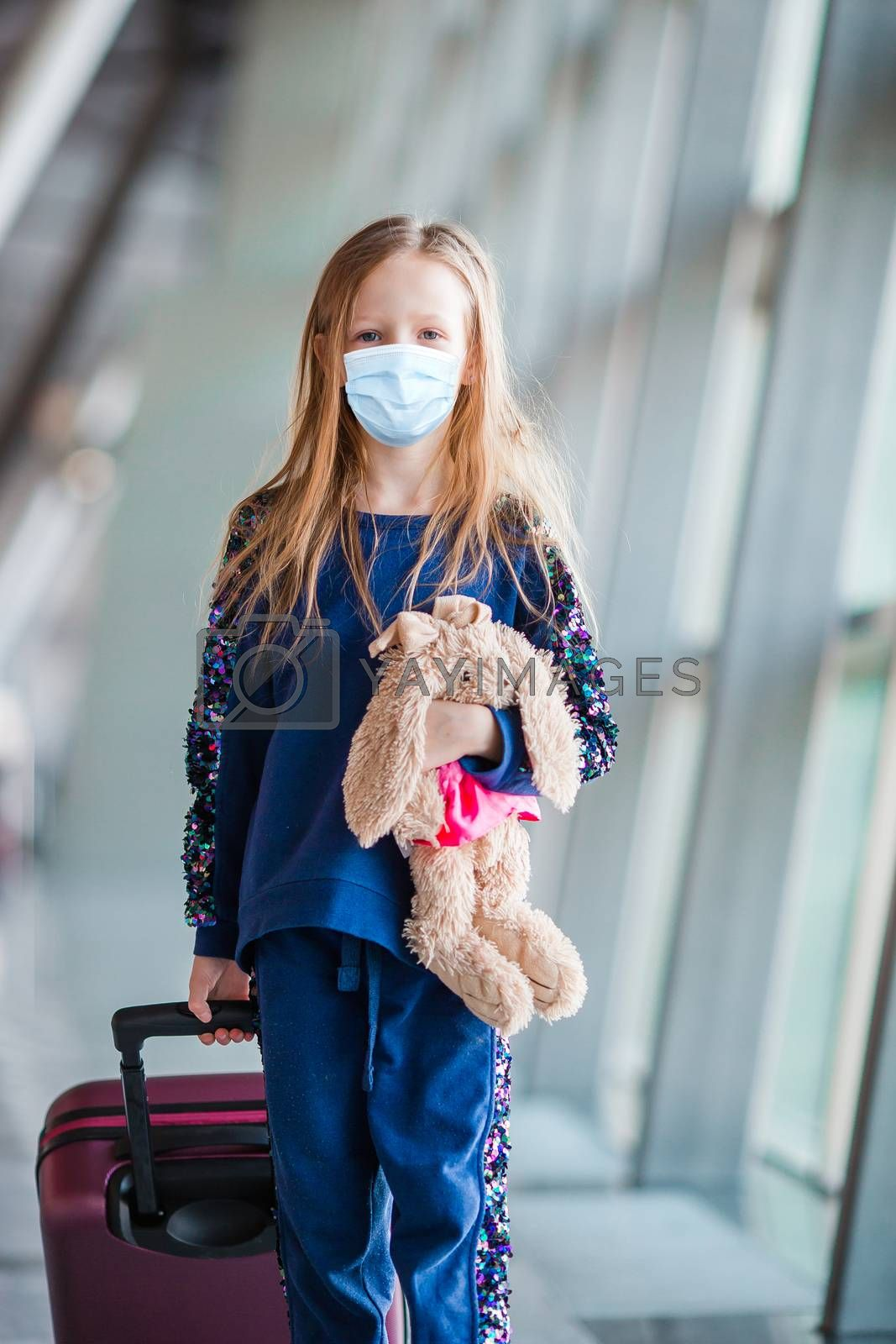 Little adorable kid with surgical mask face protection at international airport