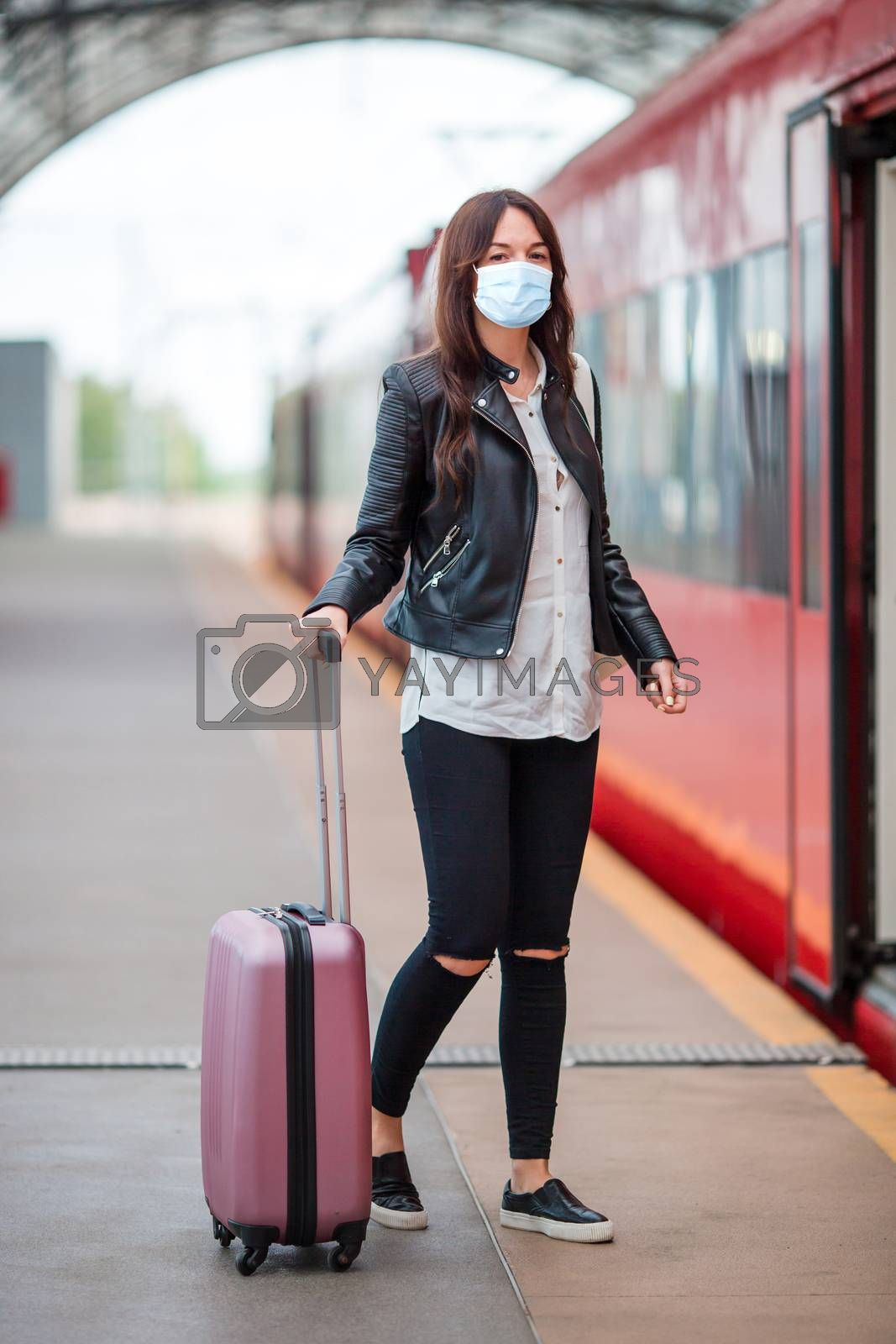 Woman wearing a mask for prevent virus with luggage on the platform waiting for aeroexpress. Protection against Coronavirus and gripp