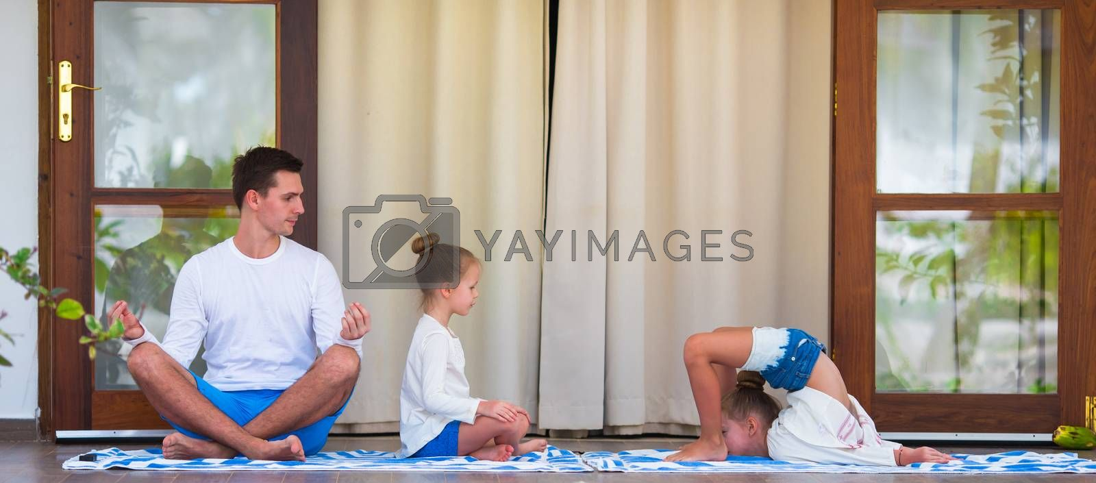 Young woman and little girl in lotus position outdoors