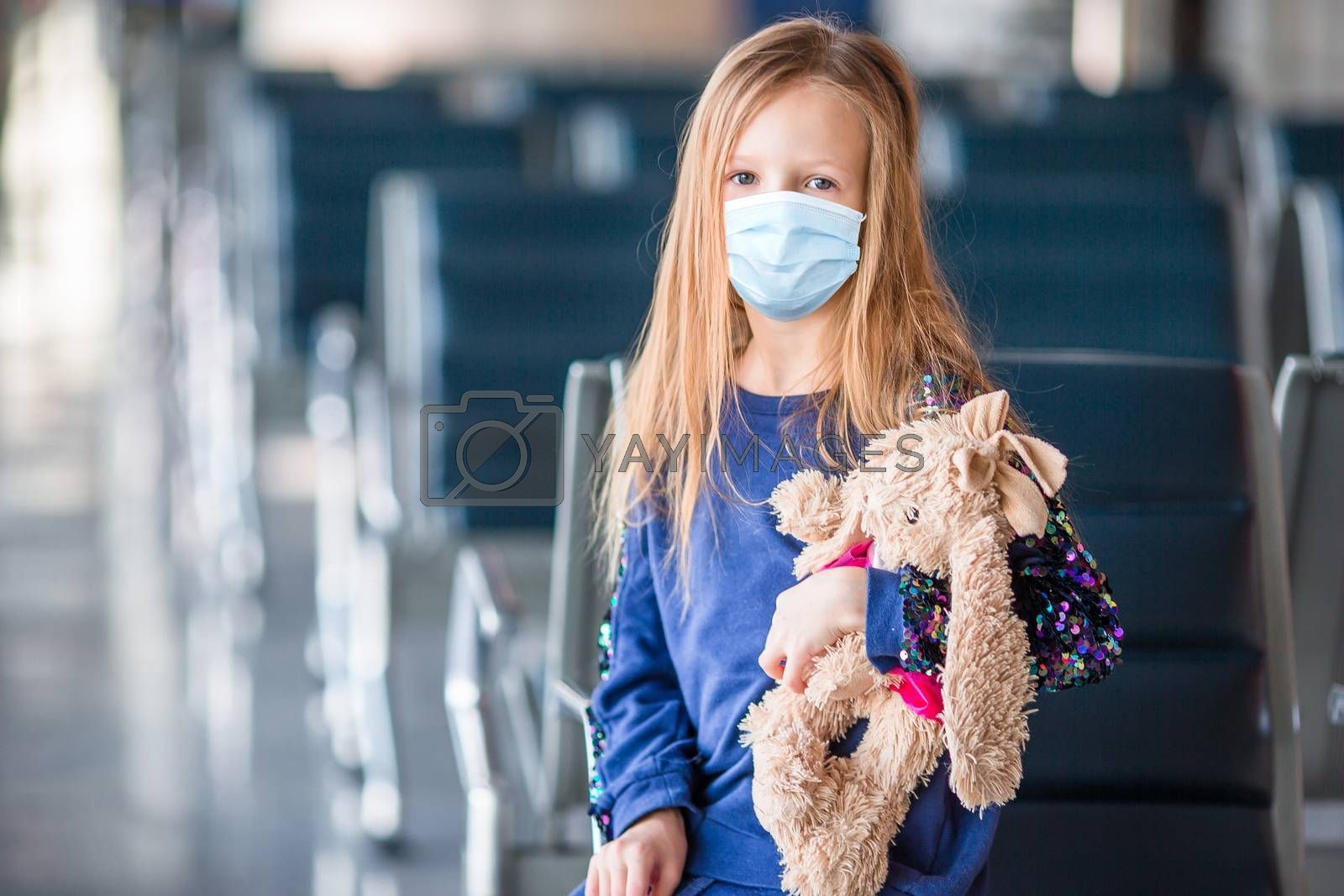 Little adorable kid with surgical mask face protection at airport train station