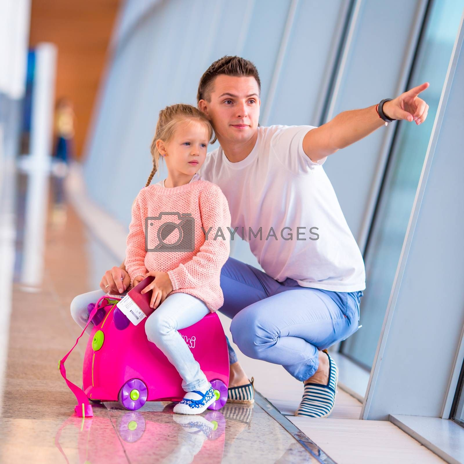 Dad and little daughter looking out the window at airport terminal