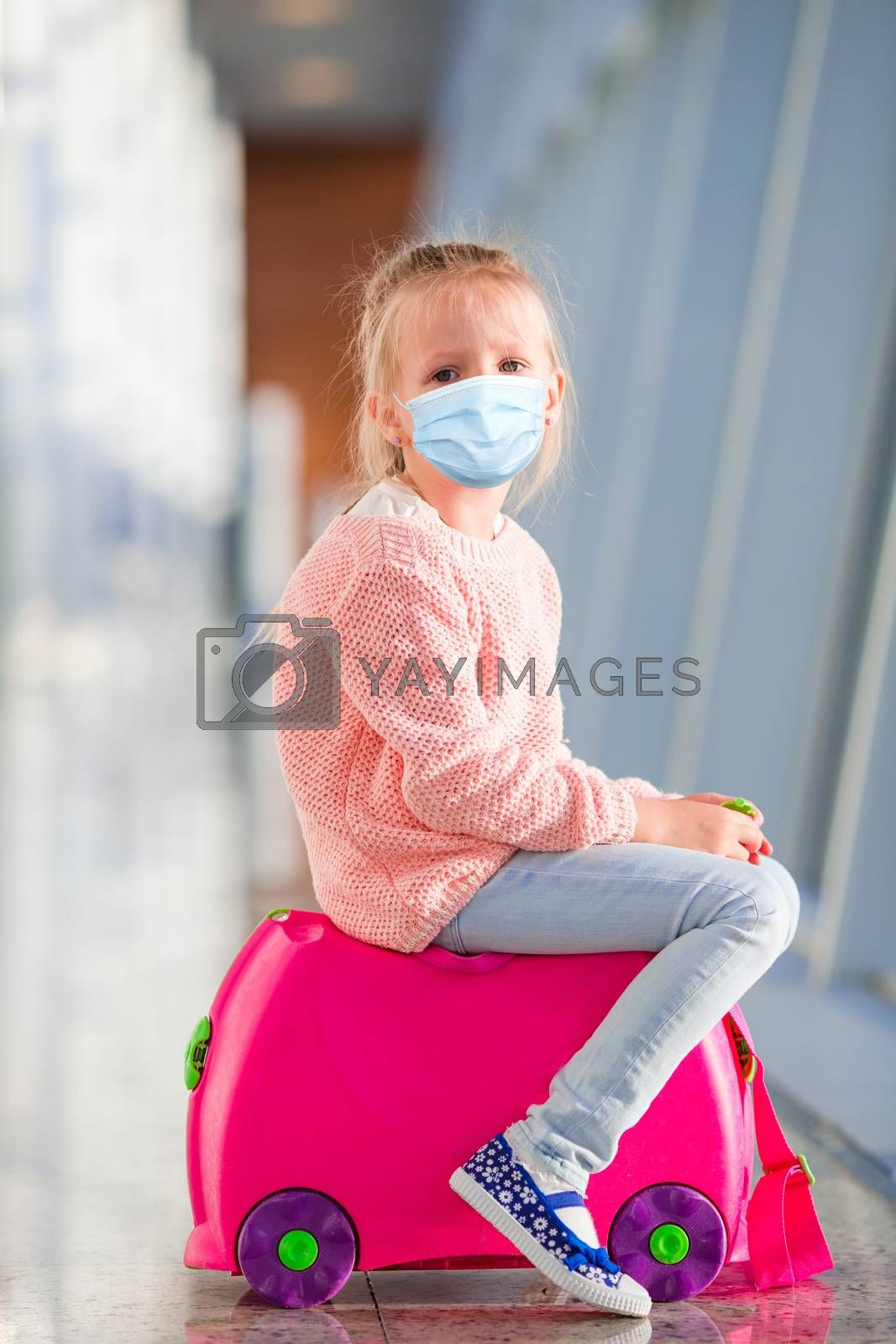 Little adorable kid wearing a mask for prevent virus with baggage in international airport. Protection against Coronavirus and gripp