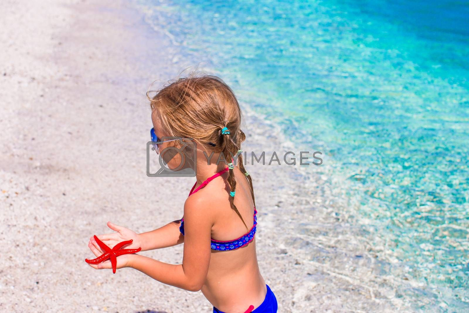 Adorable little girl with starfish at beach during summer vacation by travnikovstudio