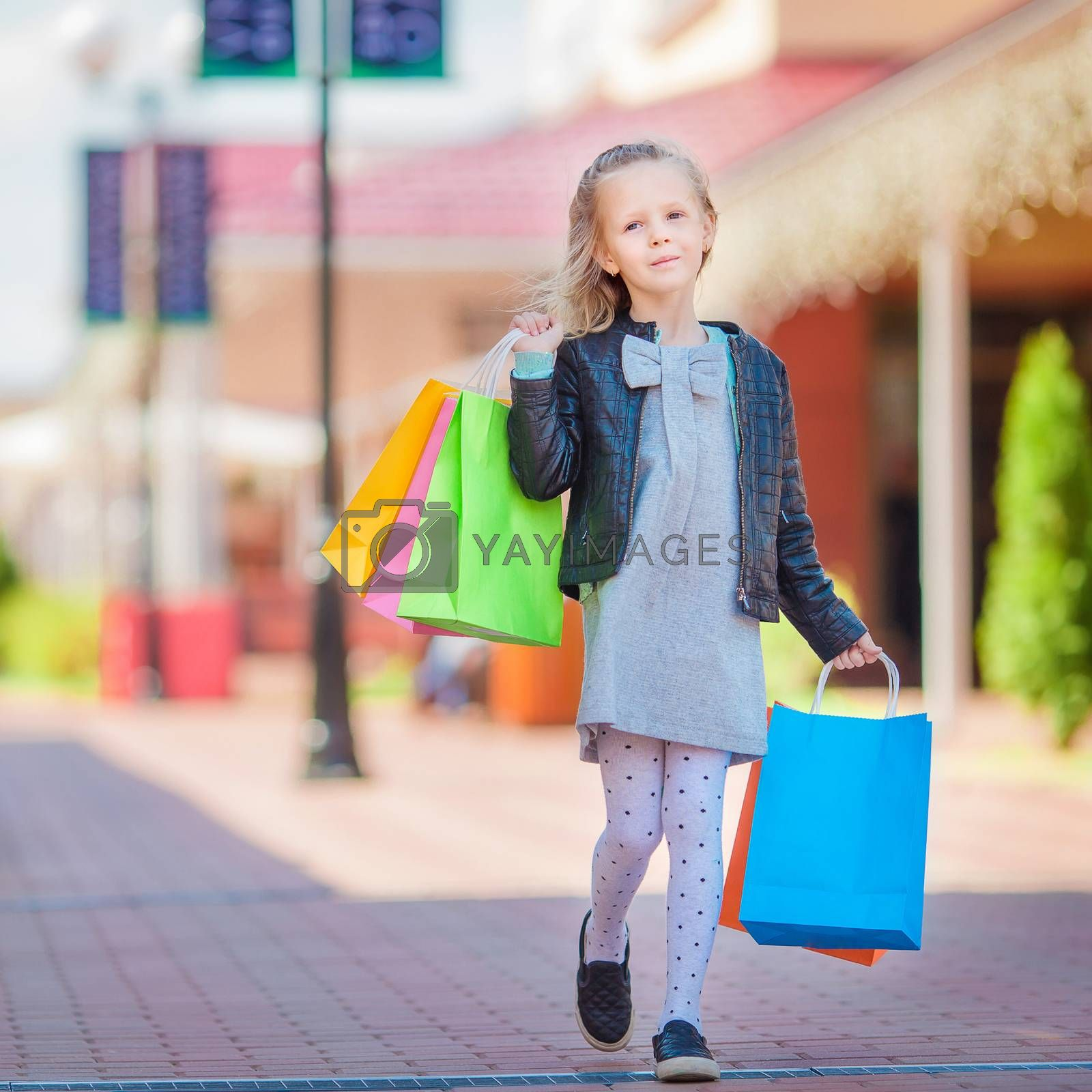 Adorable smiling little girl with shopping bags in big mall