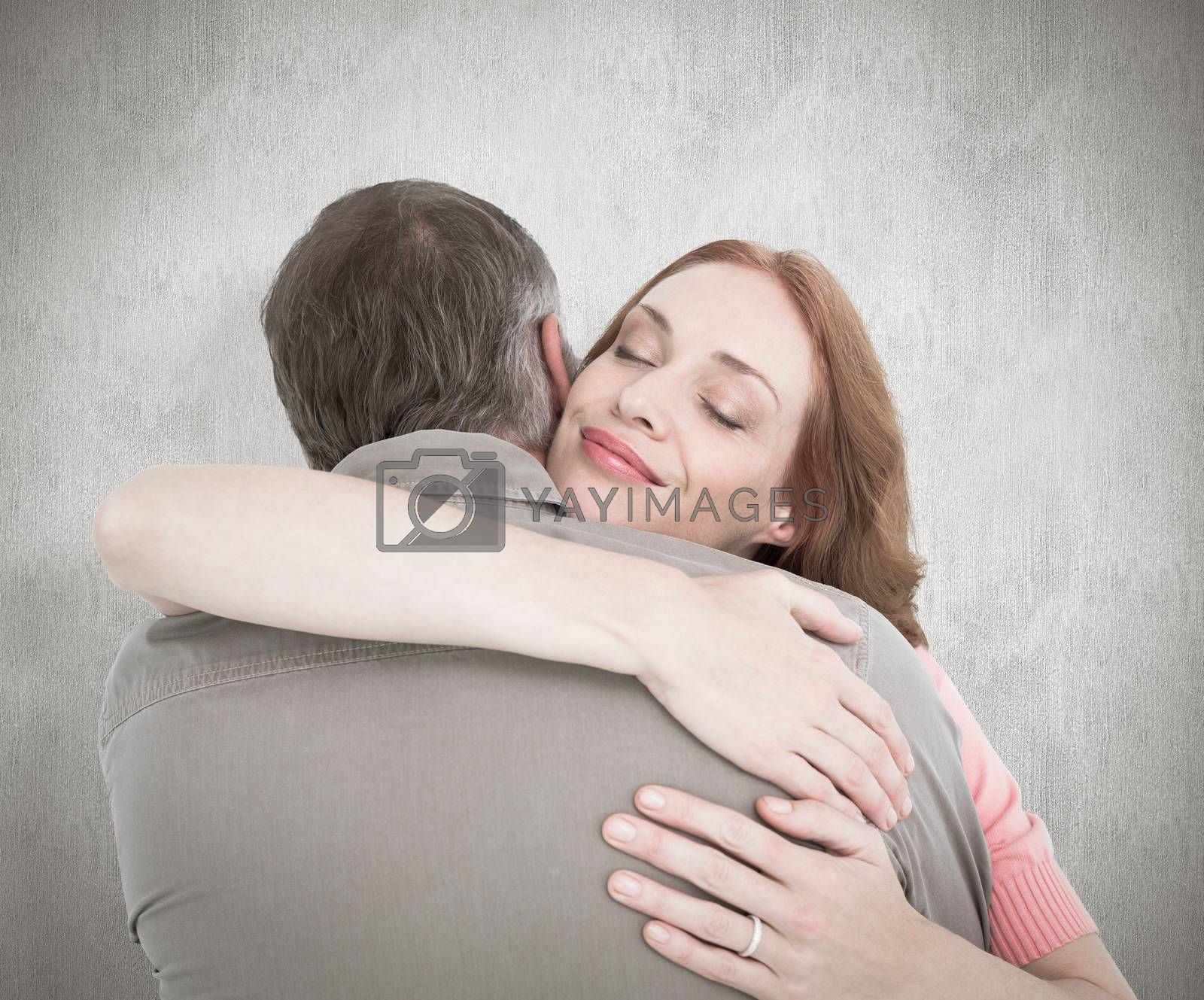 Casual couple hugging each other against white background