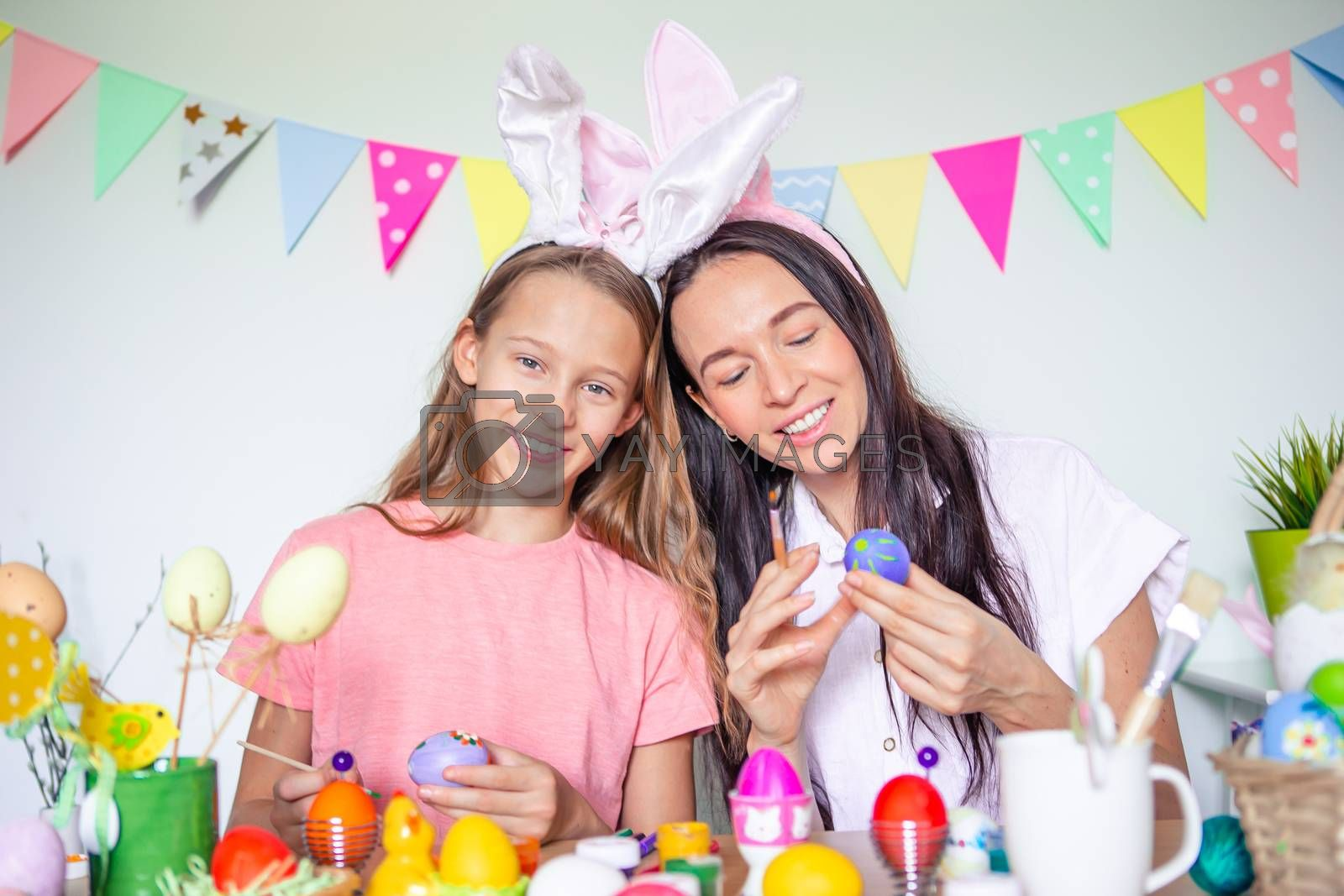 Mother and little daughter painting eggs and celebrating Easter holiday together. Happy Easter
